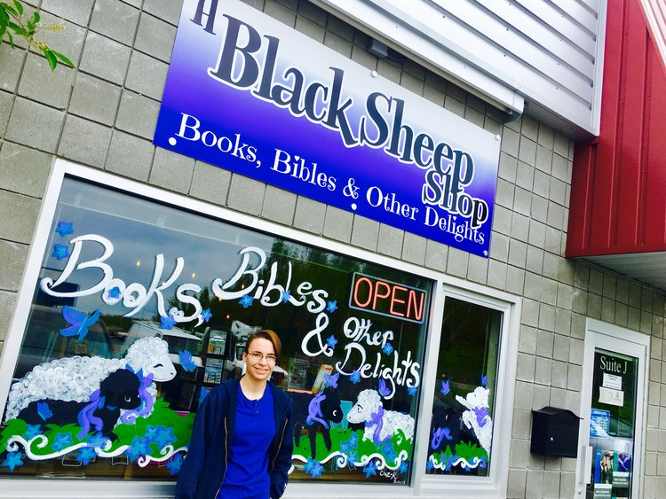 Kacey of Craz-K Designs stands with her window art outside of A Black Sheep Shop in Wasilla.