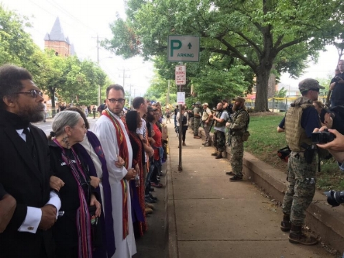 Clergy and religious leaders link arms and face armed white supremecists in Charlottesville, VA. August, 2017. (image: Christopher Mathias)