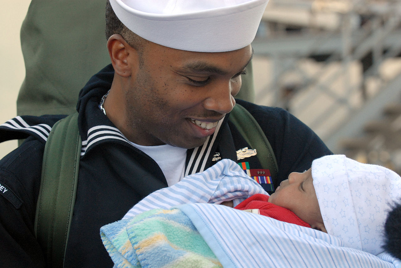 1280px-US_Navy_061224-N-9909C-009_A_proud_father_and_Sailor_from_the_destroyer_USS_Halsey_(DDG_97)_holds_his_child_for_the_first_time.jpg