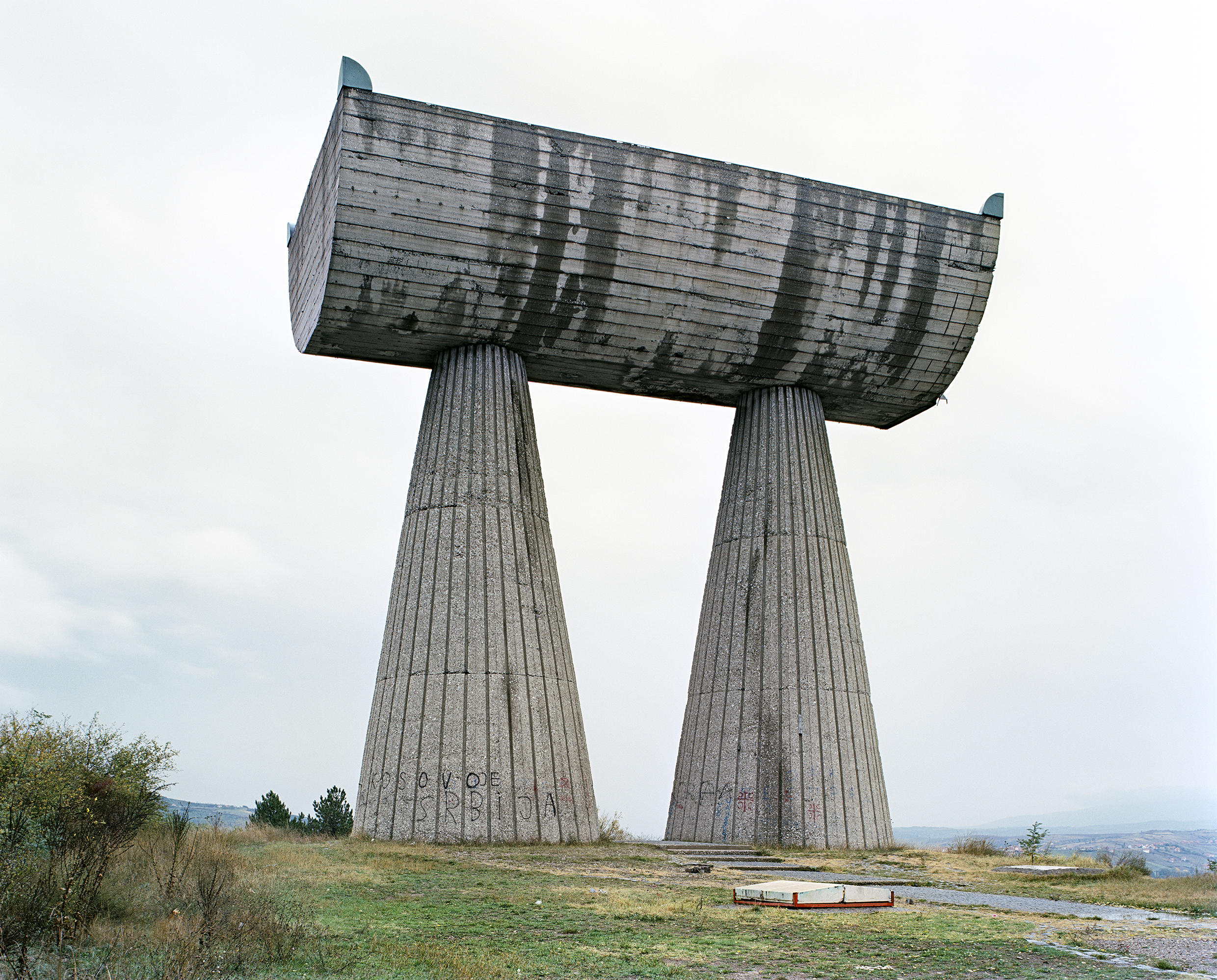 Jan Kempenaers, Mitrovića from his 2010 publication 'Spomenik'. Standing in the form of some lost Roman addition to Stonehenge, Bogdanović's huge concrete monument in the town of Mitrovica is a homage to those who were lost during fighting in World War II.