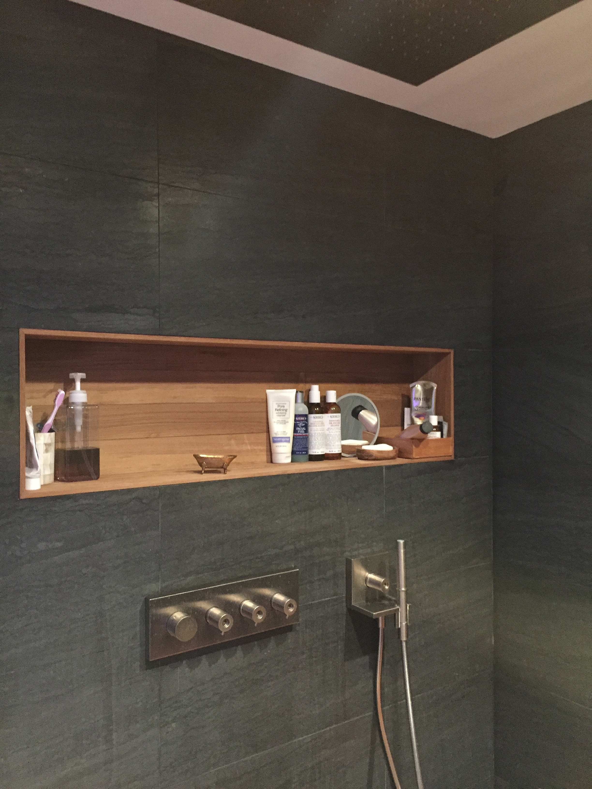 The same shower as above, here showing the  Axor Starck Heaven ceiling mounted rain head  and its many controls. Its a doozy. A teak wall nook holds all the soaps, complementing the teak shower floor and the brushed nickel fixtures.