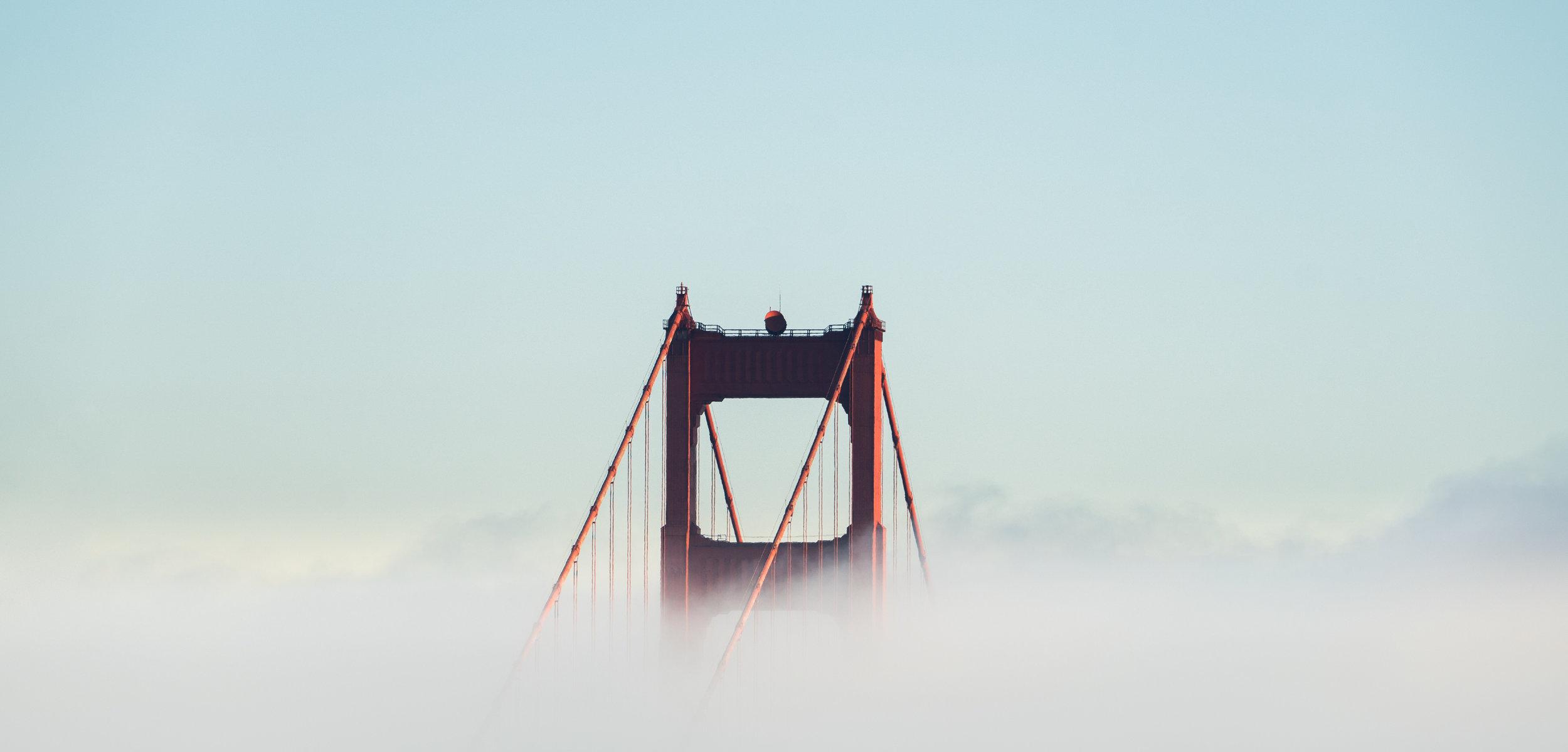 Golden Gate Bridge through the fog by  Joshua Sortino