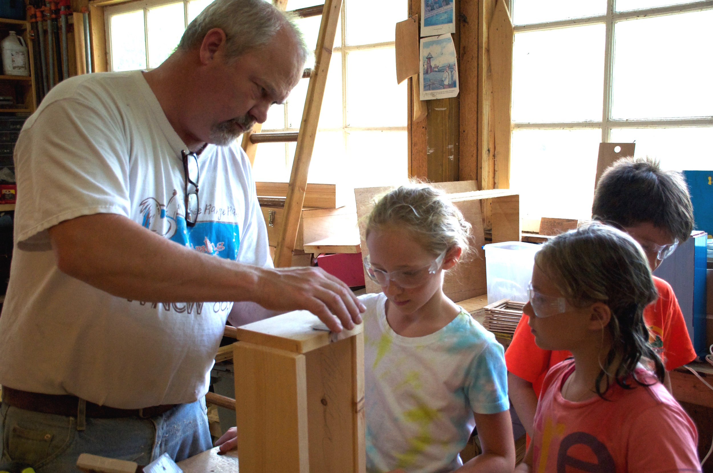 Mark working with campers in woodshop.