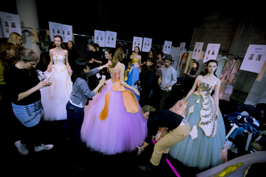 Models receive finishing touches backstage; image  via