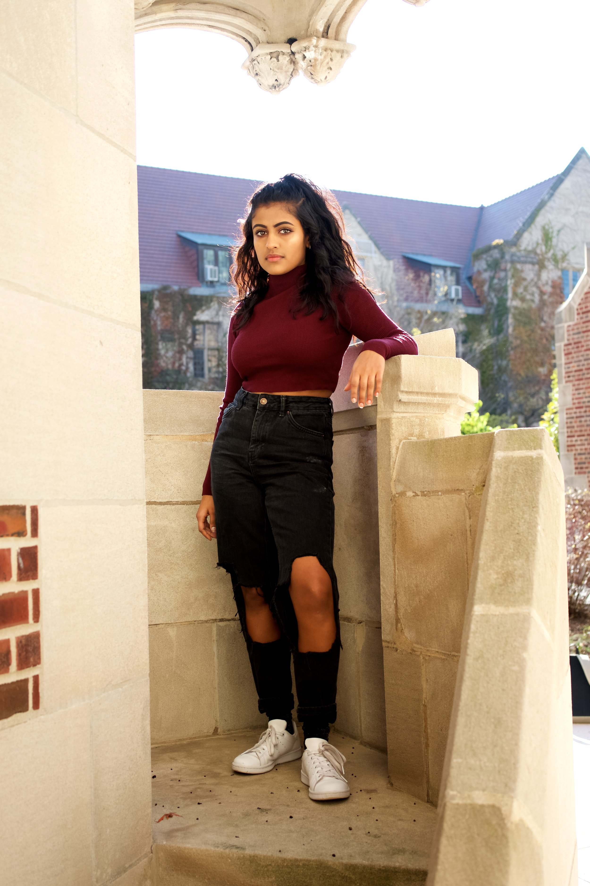 In this outfit, Yamini is wearing: a cropped turtleneck from UNIF, jeans from Topshop, and Adidas Stan Smiths.