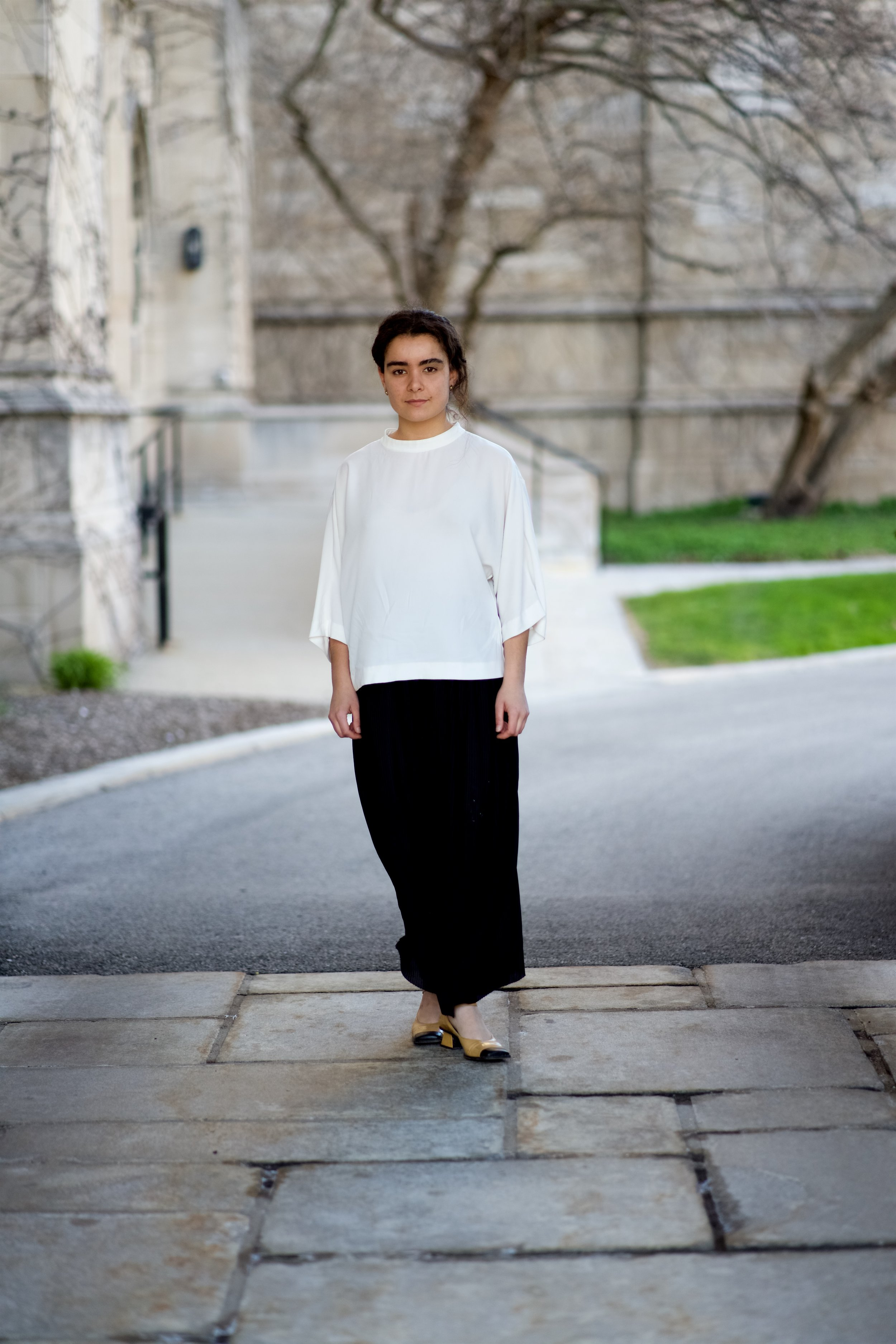 I'm black ribbed flowy wide-leg trousers (thrifted),a Uniqlo white mock neck short-sleeve shirt and Miu Miu shoes (thrifted).