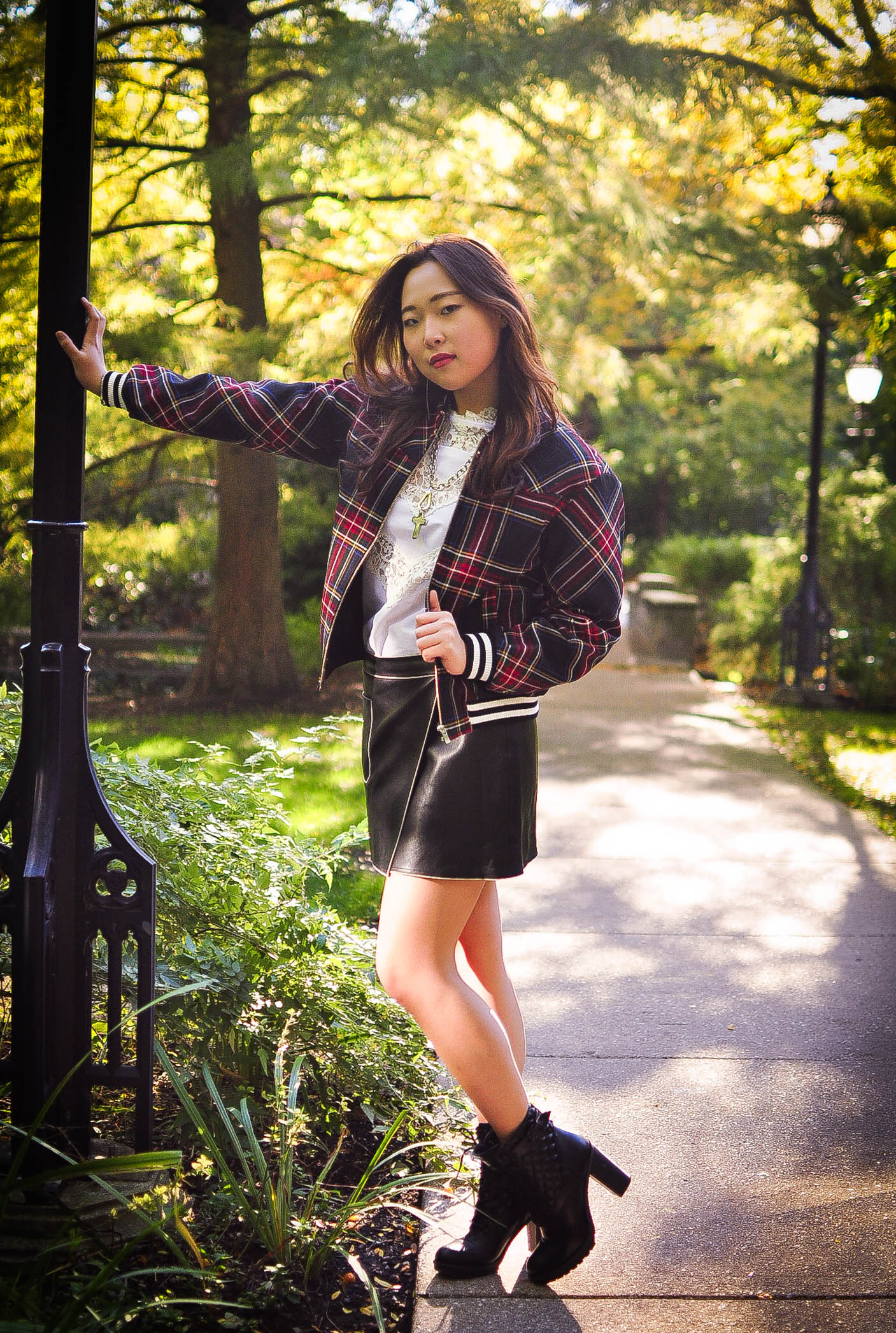 For this look, I'm wearing a tartan bomber jacket draped over a white lace blouse, coupled with a leather skirt, all from Korea and chunky boots from Guess.