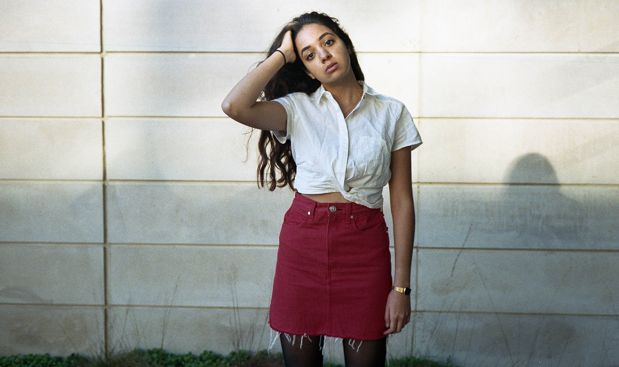 The cropped white button-down is from Free People, red skirt from Rag and Bone. The suede, brown, knee-high boots are from Urban Outfitters. The accessories are a hamsa (evil eye) necklace, tiny gold hoop earrings, gold casio watch