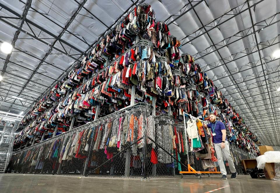 A three-tiered conveyor system to store clothing is employed by a thredUP facility in Phoenix, Arizona. Source  via .