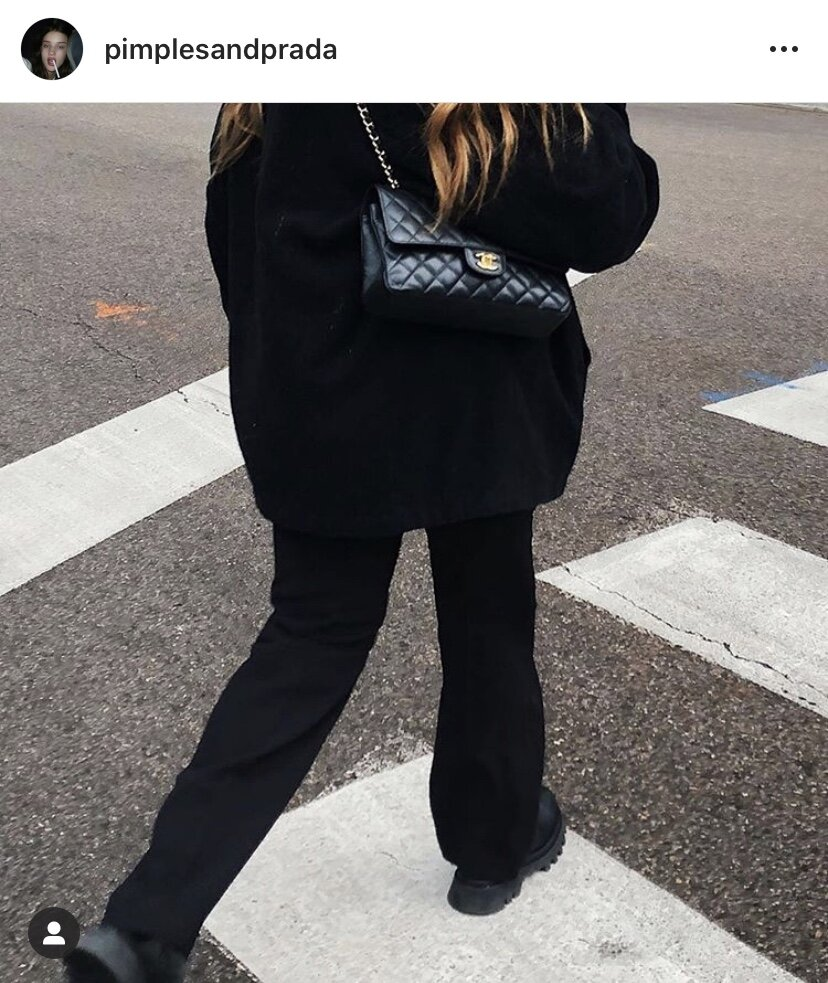 Potter crossing the street in an all black outfit, punctuated by a classic Chanel double flap. Image  Via