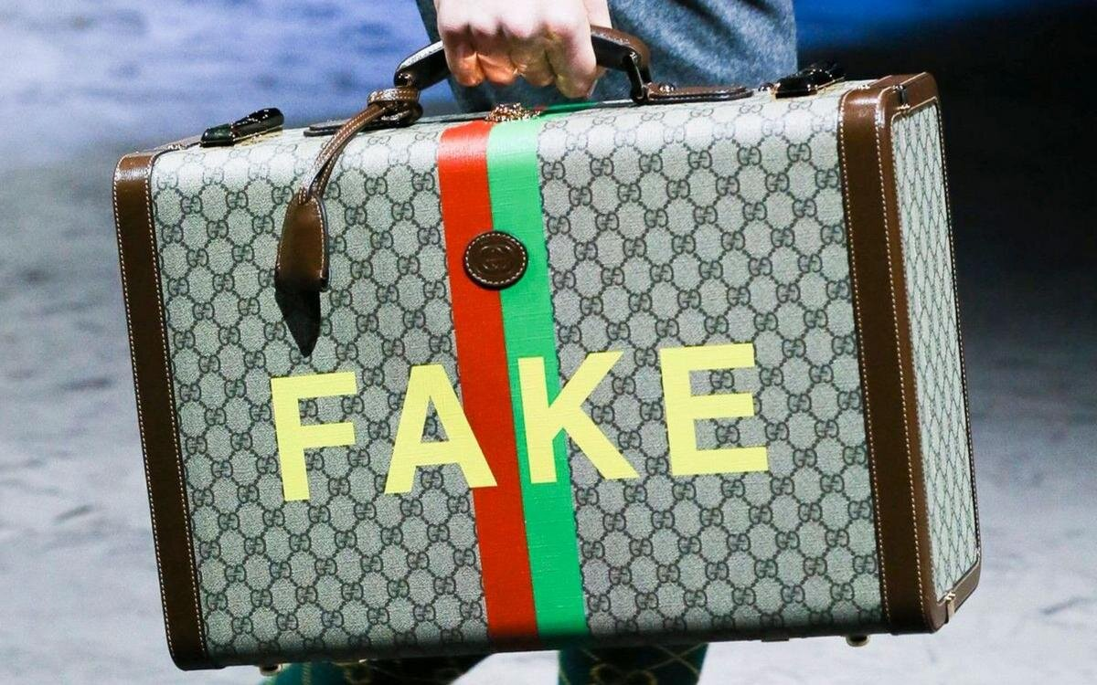 A hard suitcase from the Fake/Not capsule collection, first unveiled in Gucci's AW20 show, prominently displaying 'FAKE' against Gucci's iconic bicolor striped motif. Image  Via