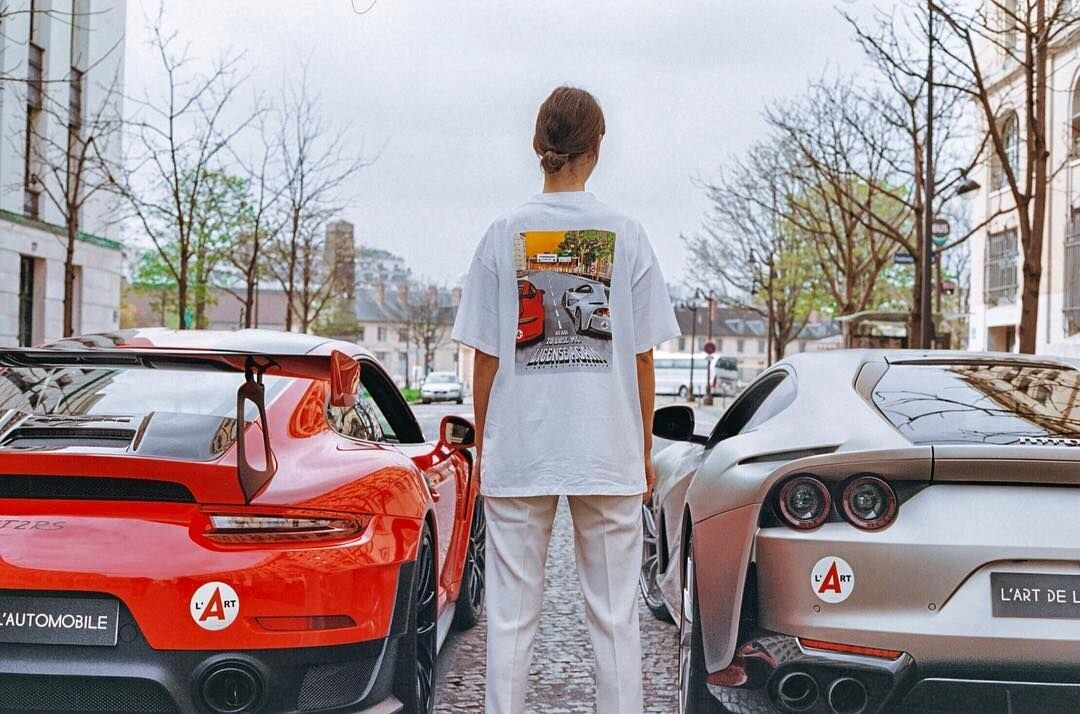 A model wears a L'ART tee depicting the exact scene she is standing in, featuring a Porsche 911 GT2RS and Ferrari 812 Superfast. Image  Via