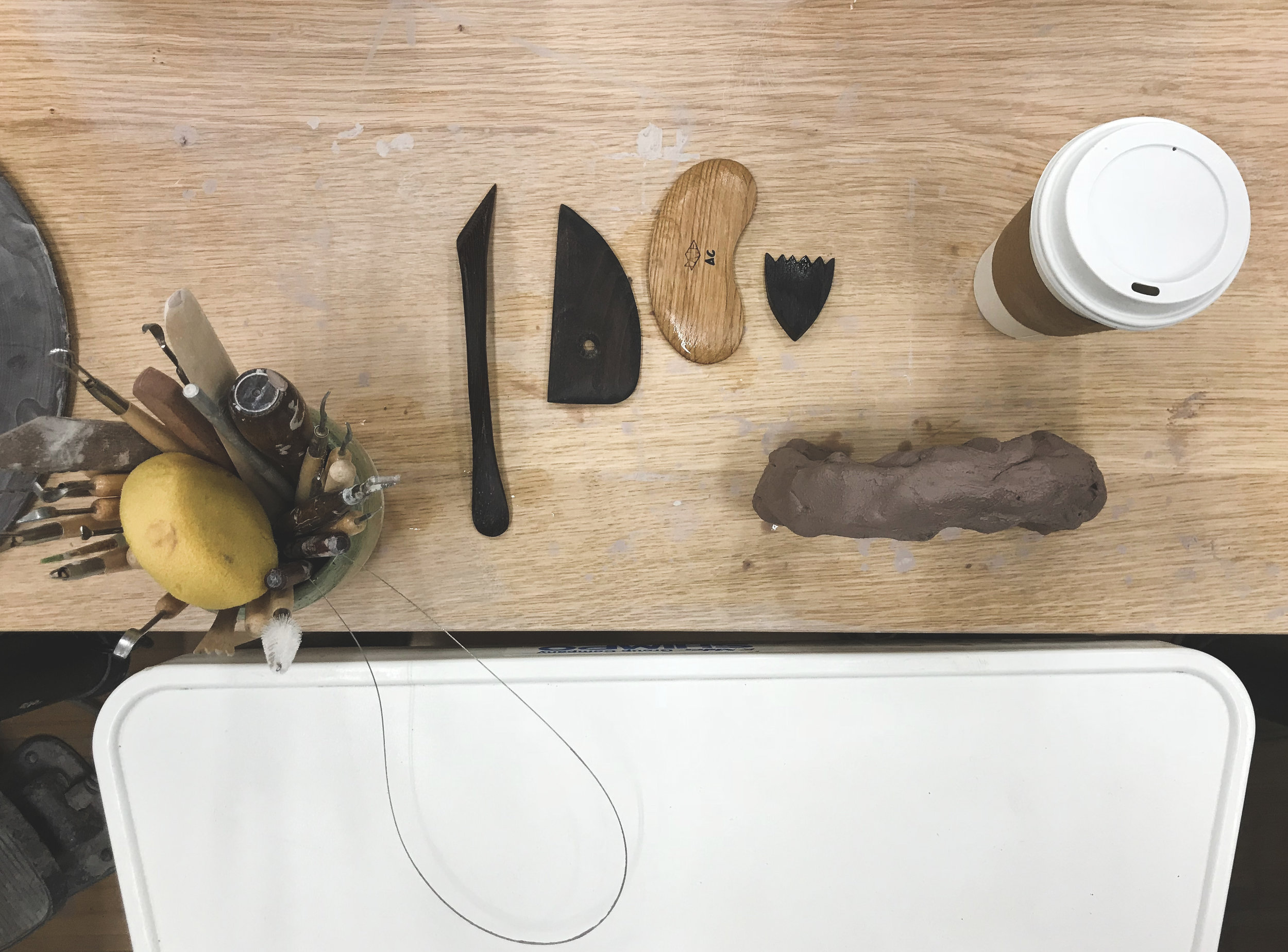 Tools in their jar. Tools washed clean and ready to go again. Green tea. And a lump of clay that didn't work out. It's drying in this form, and I'll rewedge it to start again as another form for another day.