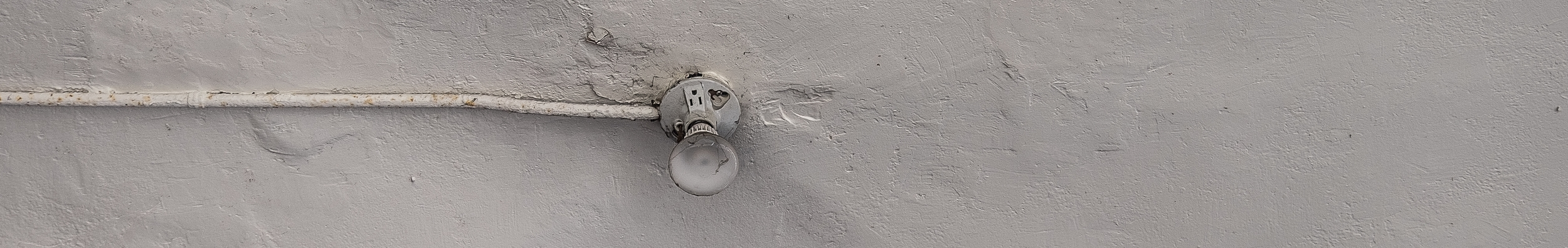bare lightbulb on bare wall