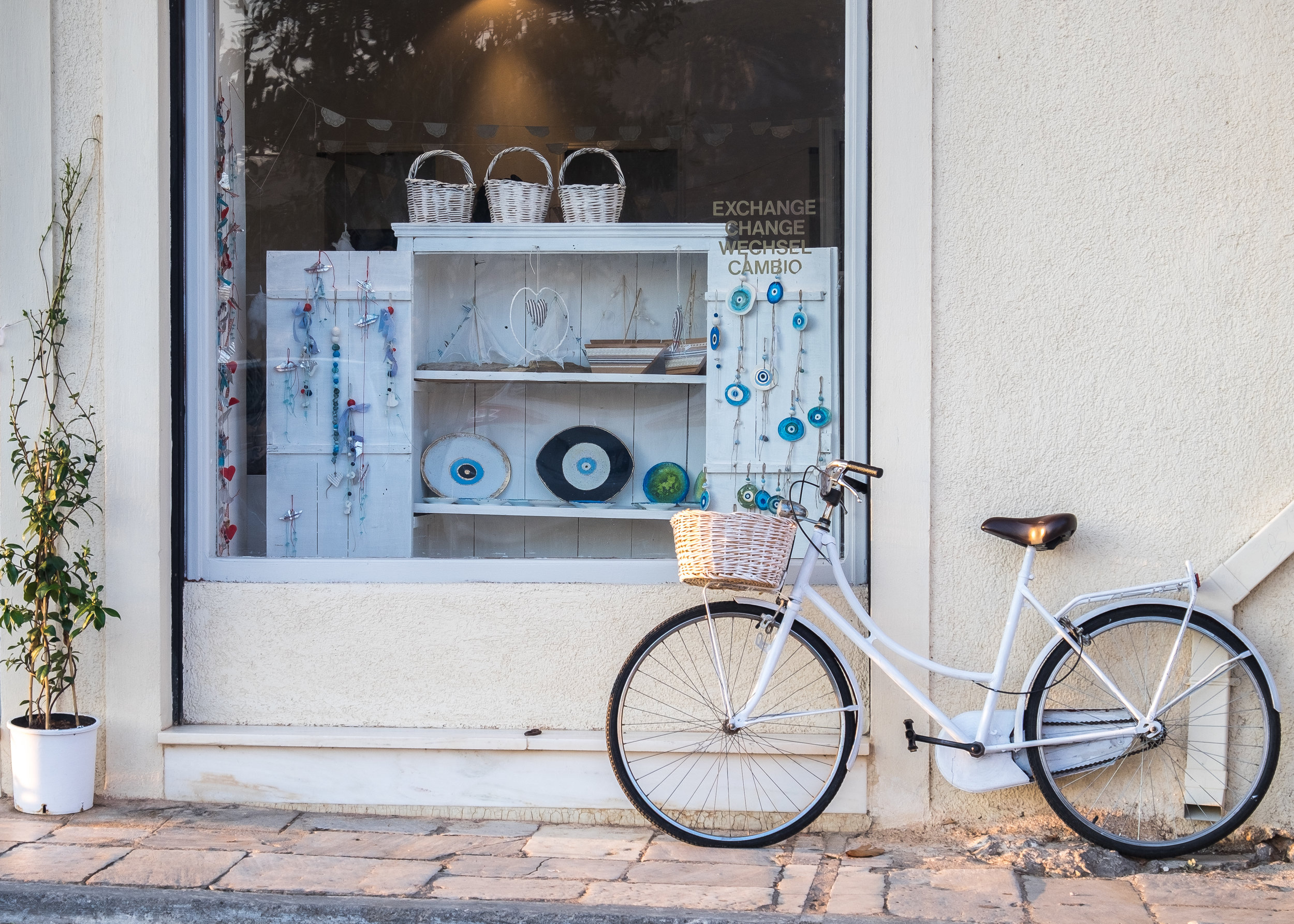 bike with basket in front of quaint storefront with baskets and pottery