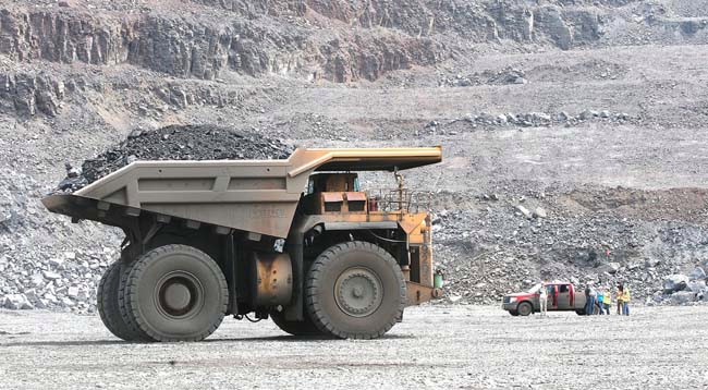 A truck carrying more than 240 tons of taconite ore takes a load to the crusher in the Thunderbird Mine of United Taconite near Virginia, Minn., on Aug. 7, 2014. (Forum News Service: Bob King)