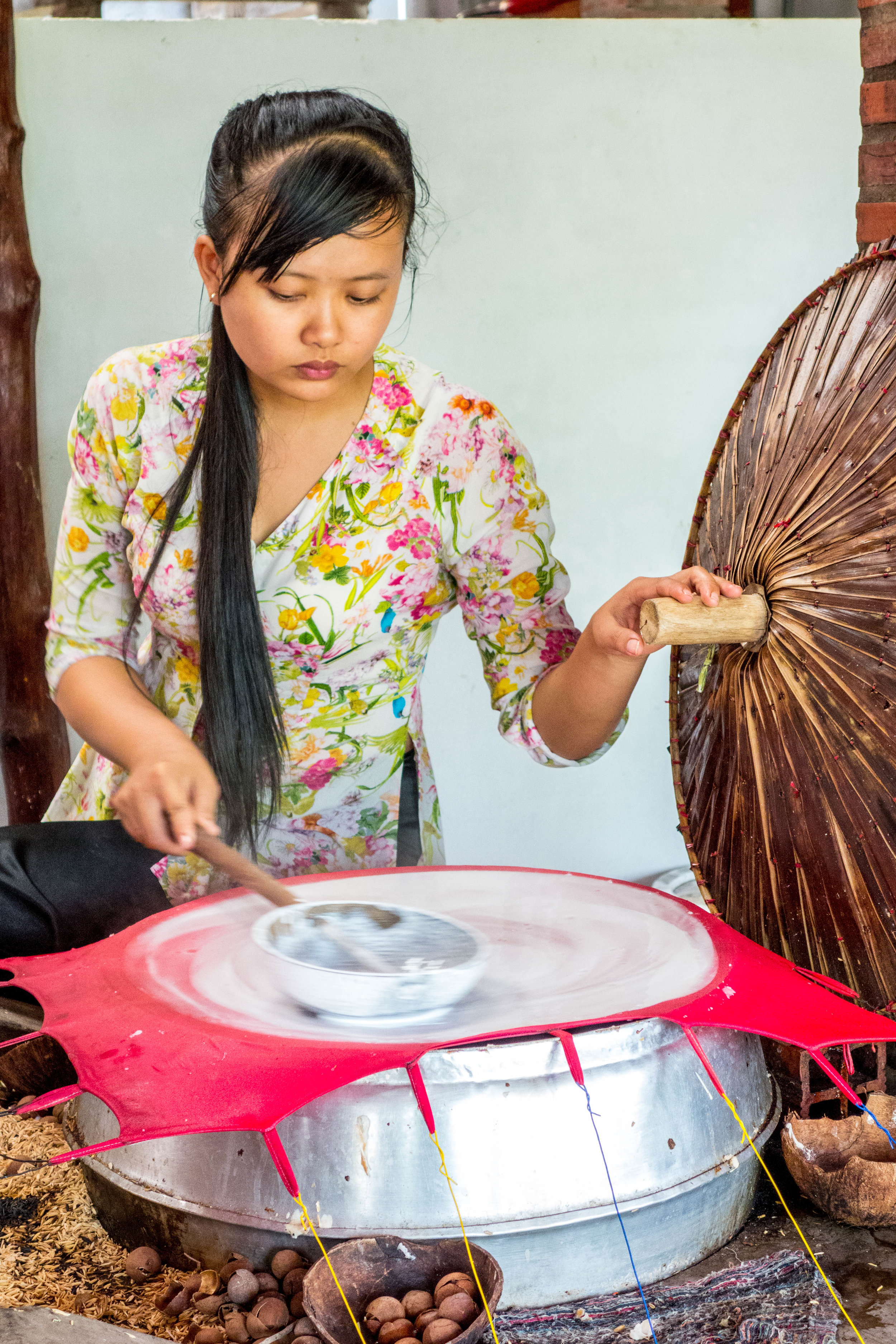 A young woman making rice paper.