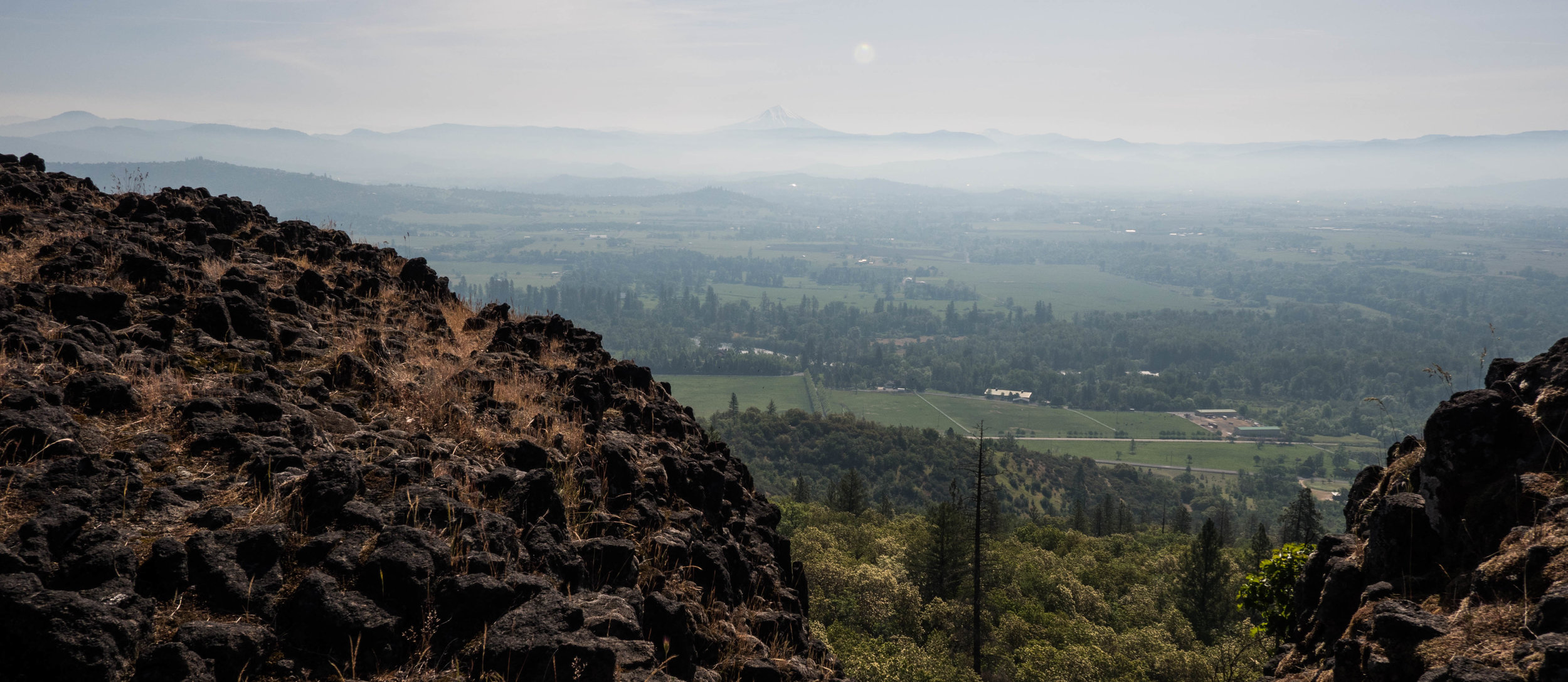 Remnants of lava rock on top of the mesa. The communities of the Rogue Valley below.