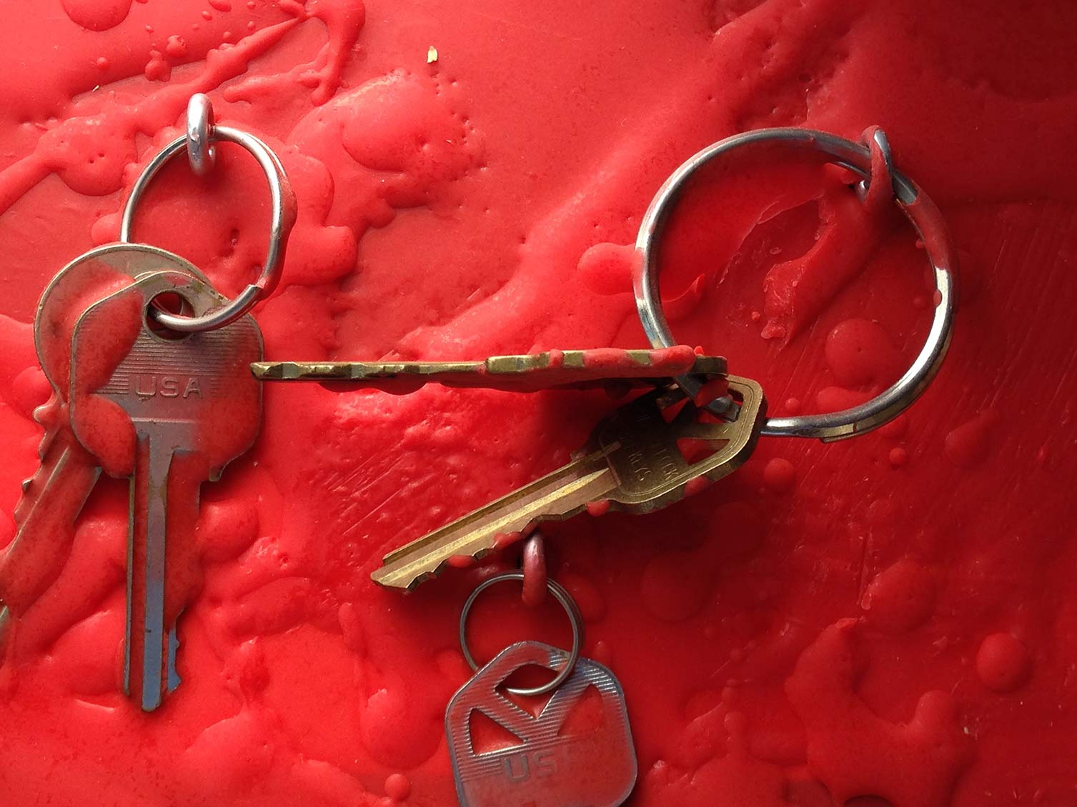 Repossessed homeowner keys drenched in red encaustic wax.