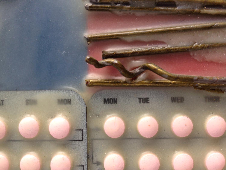 72 pill packs alternate with coat hangers as flag stripes.