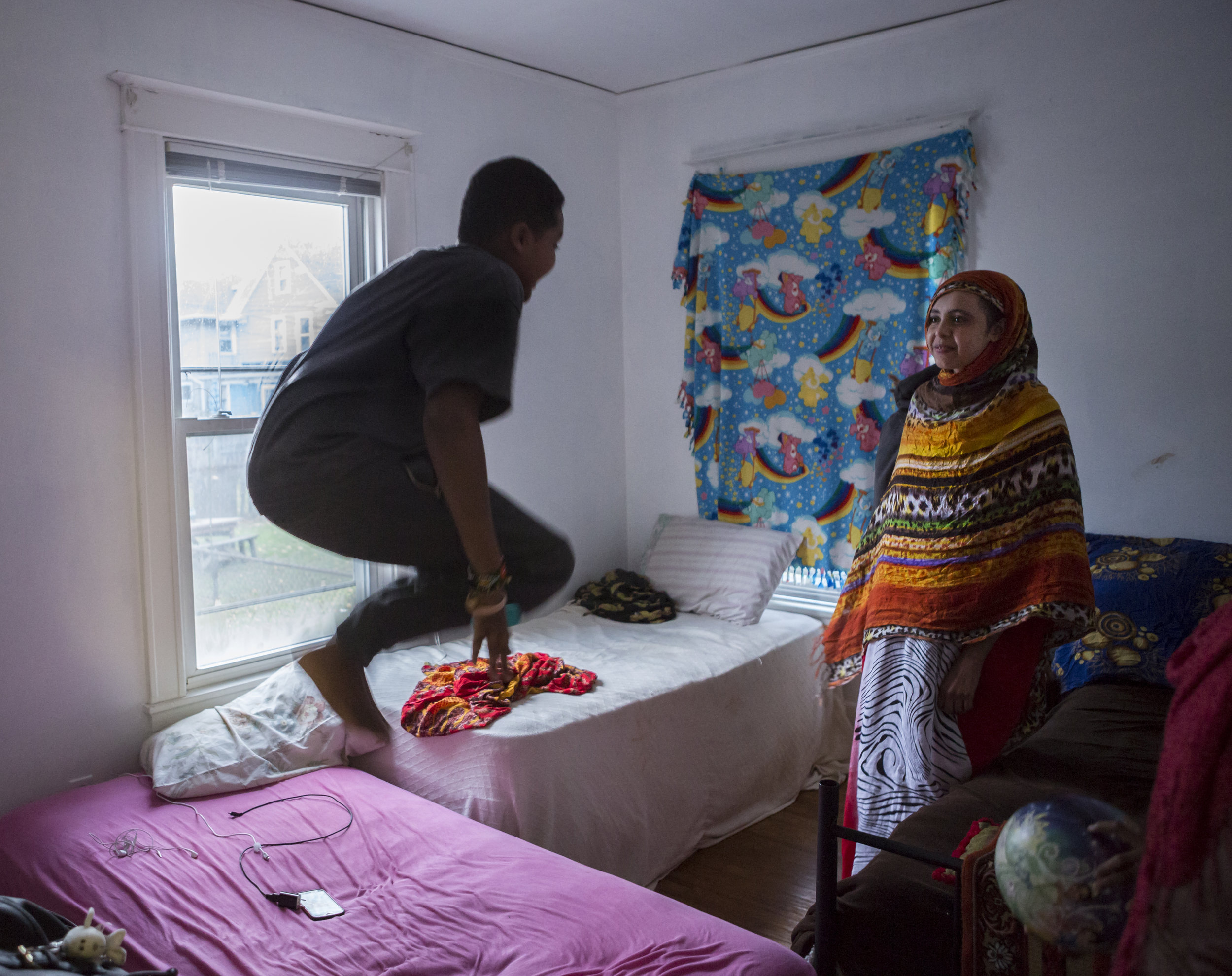 Abdullahi jumps on one of his nine sister's beds as his elder sister Rodha, nicknamed Haifa, looks on. This bedroom is shared by 3 sisters. Dec 1, 2016