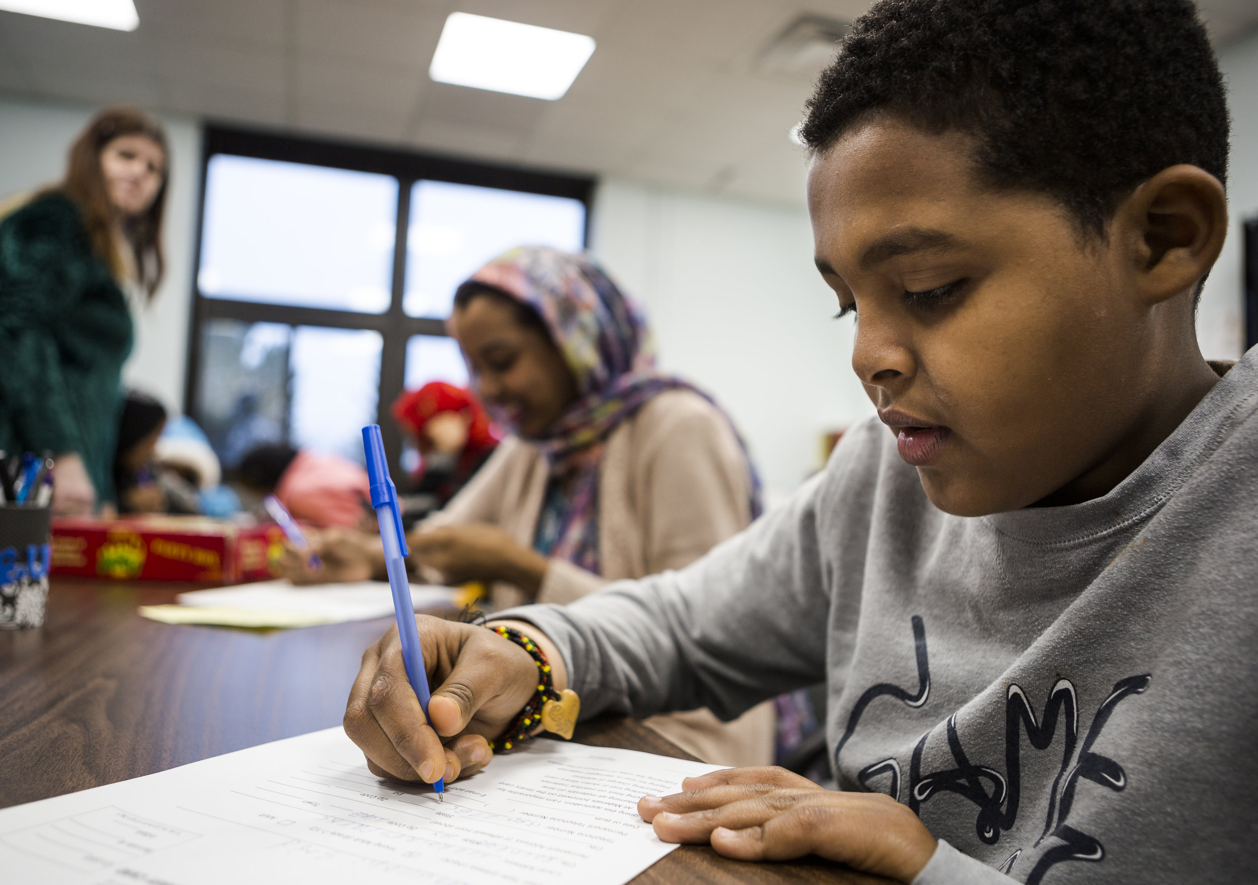 At the local library, Abdullahi and his sisters fill out forms at the Maplewood Community Library for the first time. Abdullahi's exact birthday is unknown to him or his family, so his sisters decided January 1st would be his birthday recorded on the form. The children will also be able to take advantage of homework-help and tutoring sessions at the library which is roughly a fifteen-minute walk from their home. Dec 2, 2016