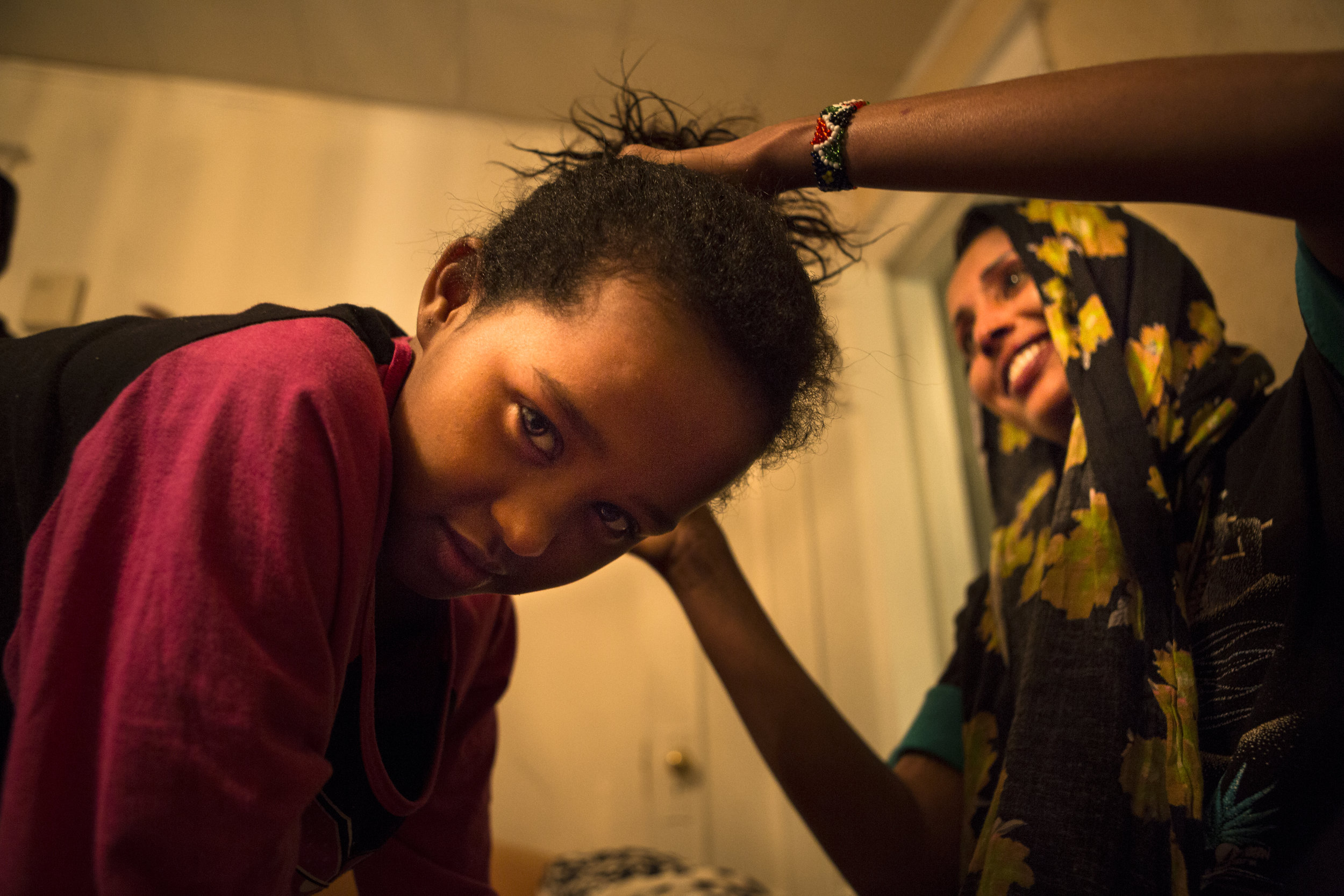 Najma Said gets her hair tied by her older sister, Husna. Rochester, NY. Dec 3, 2016.