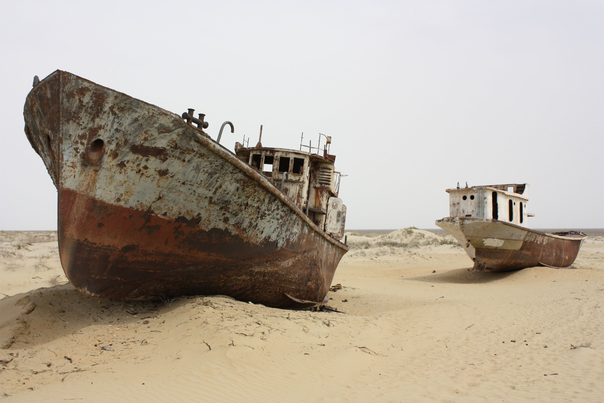Boats marooned on sand where the Aral Sea once existed - now due to industries like water thirsty cotton, little remains of the water body.