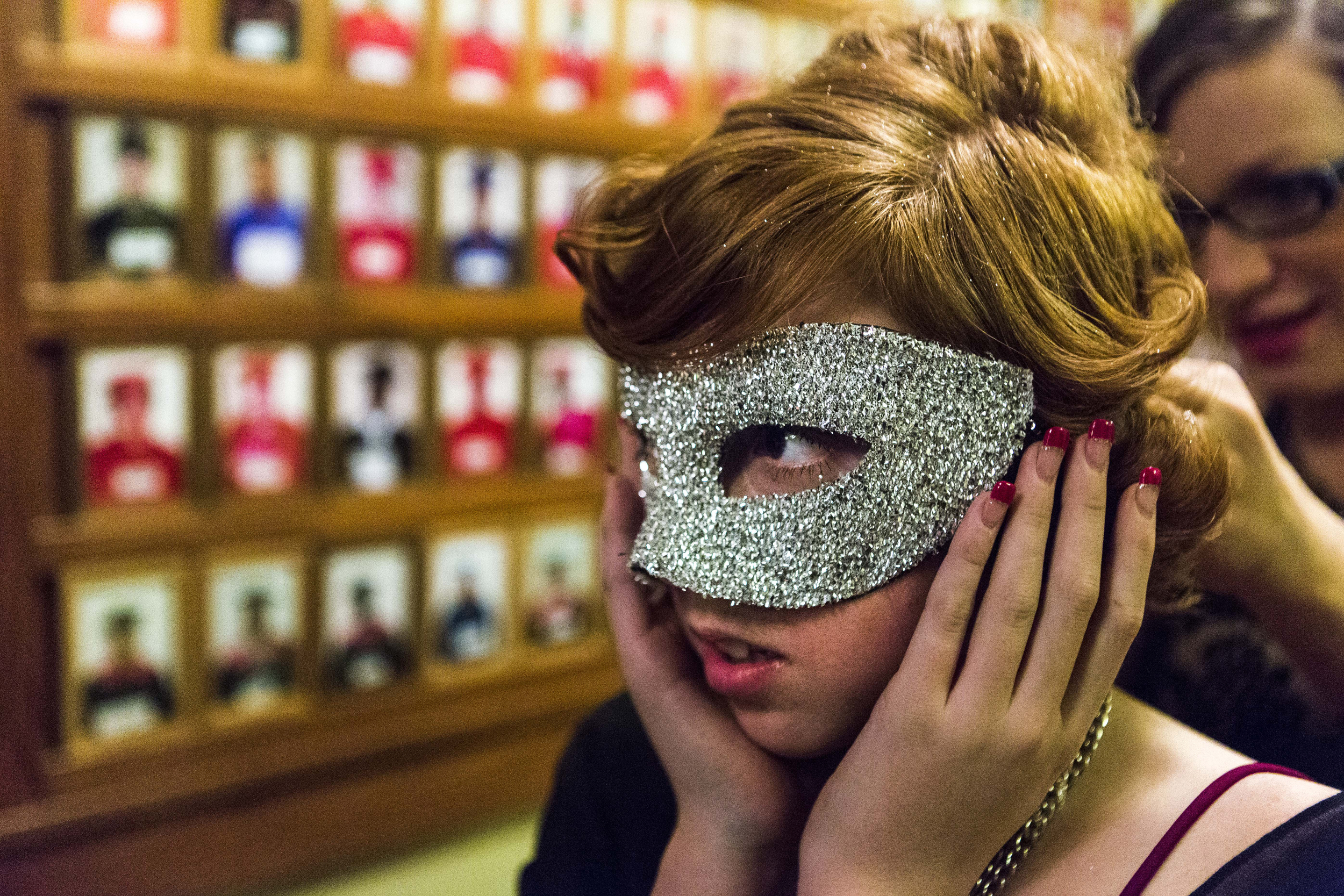 As part of her outfit, a teenager puts on a mask during the Lighthouse's Prom in Lincoln, Nebraska.Lighthouse, an organization that serves as a refuge for at-risk children for over 25 years, organized their own dance for those who could not afford to attend their school's prom. Everything from getting their nails to the the outfits themselves were donated.