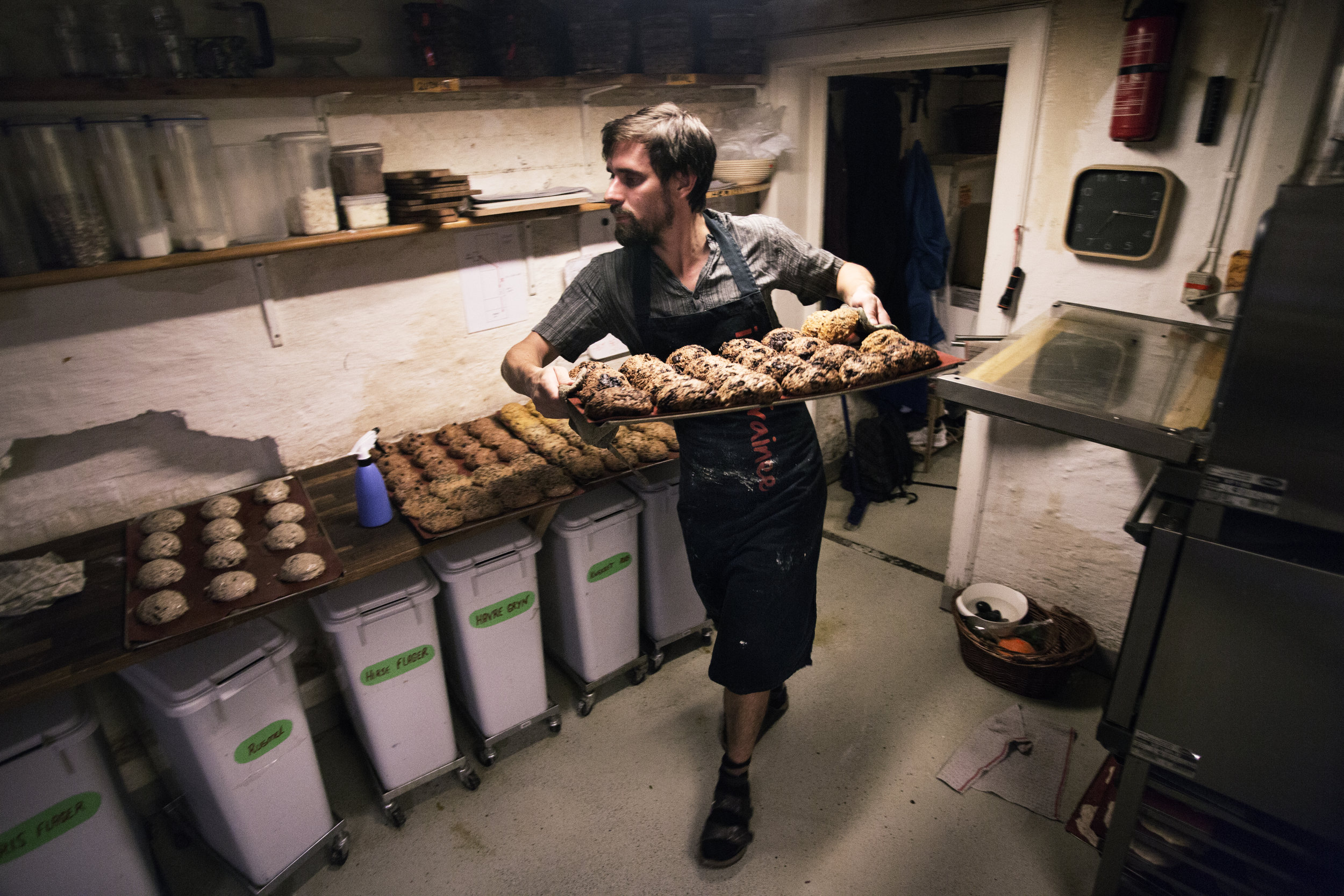 Mathieu Crespe pulls scones from in the oven in the basement of the Ganeyfryd, an organic market, early one morning in Aarhus, Denmark.
