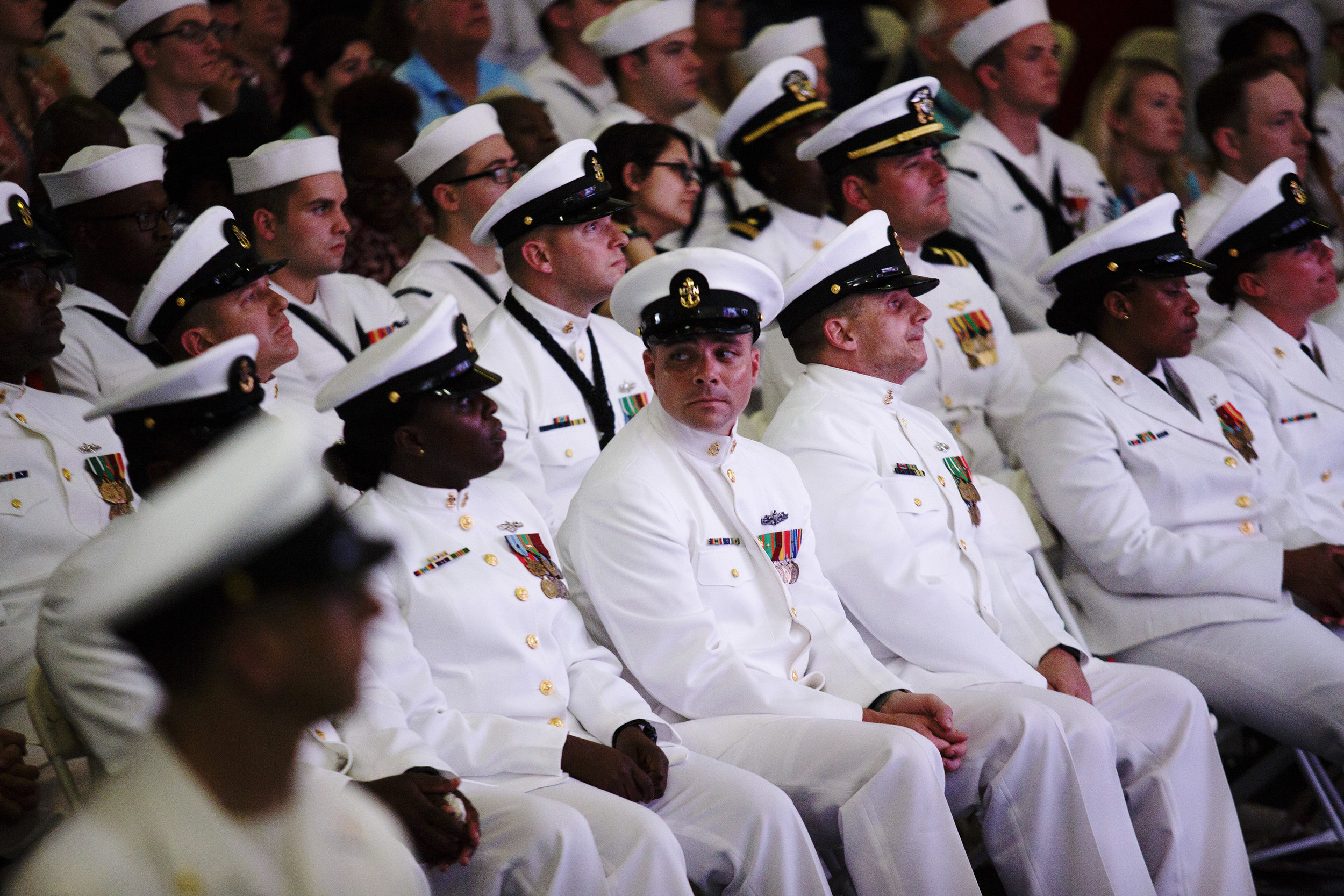 Members of the United States Navy watch the commissioning of the USS Gerald R. Ford (CVN 78) at the Naval Station Norfolk in Norfolk, Virginia. A crowd of nearly 10,000 individuals gathered to watch the commissioning ceremony for the Navy's newest aircraft carrier.