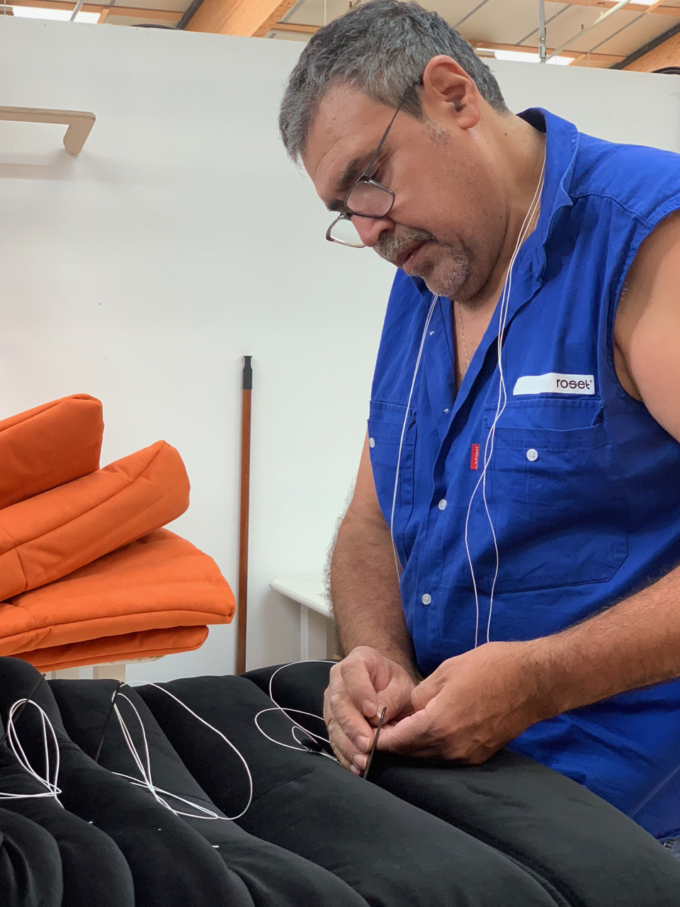 An upholsterer with more than 20 yrs. of experience hand-tufts a velvet Togo