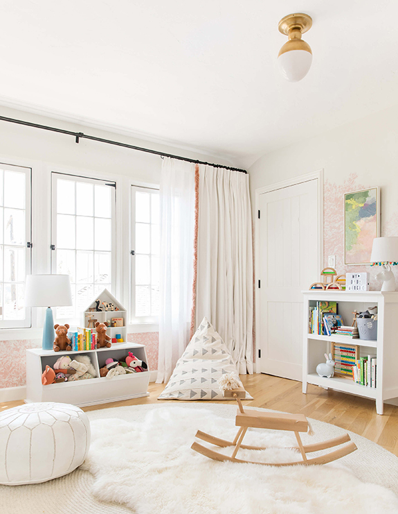 Emily Henderson   chose draperies in a neutral linen with playful pink fringe for her daughter's nursery.