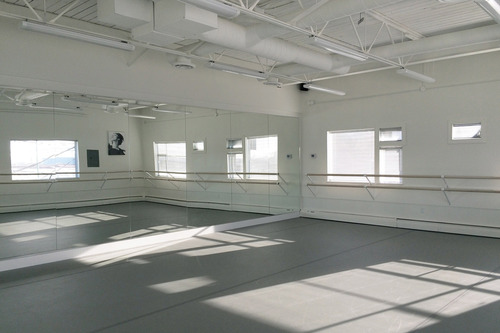 "NIJINSKY STUDIO - Our Nijinsky Studio is 800 SF and ideal for regular classes for all ages, private lessons, as well as Conditioning and Rhythmic Stretch sessions. With an abundance of natural light, exposed high ceilings, air-conditioning, and 8 foot mirrors spanning the two walls opposite the windowed walls, Nijinsky provides as our second state of the art dance studio. Also boasting top-of-the line floating Harlequin maple sprung floors, Harlequin ""Cascade"" marley flooring, Harlequin maple hardwood barres, and custom-made barre mounts designed and built to spec for our dancers."