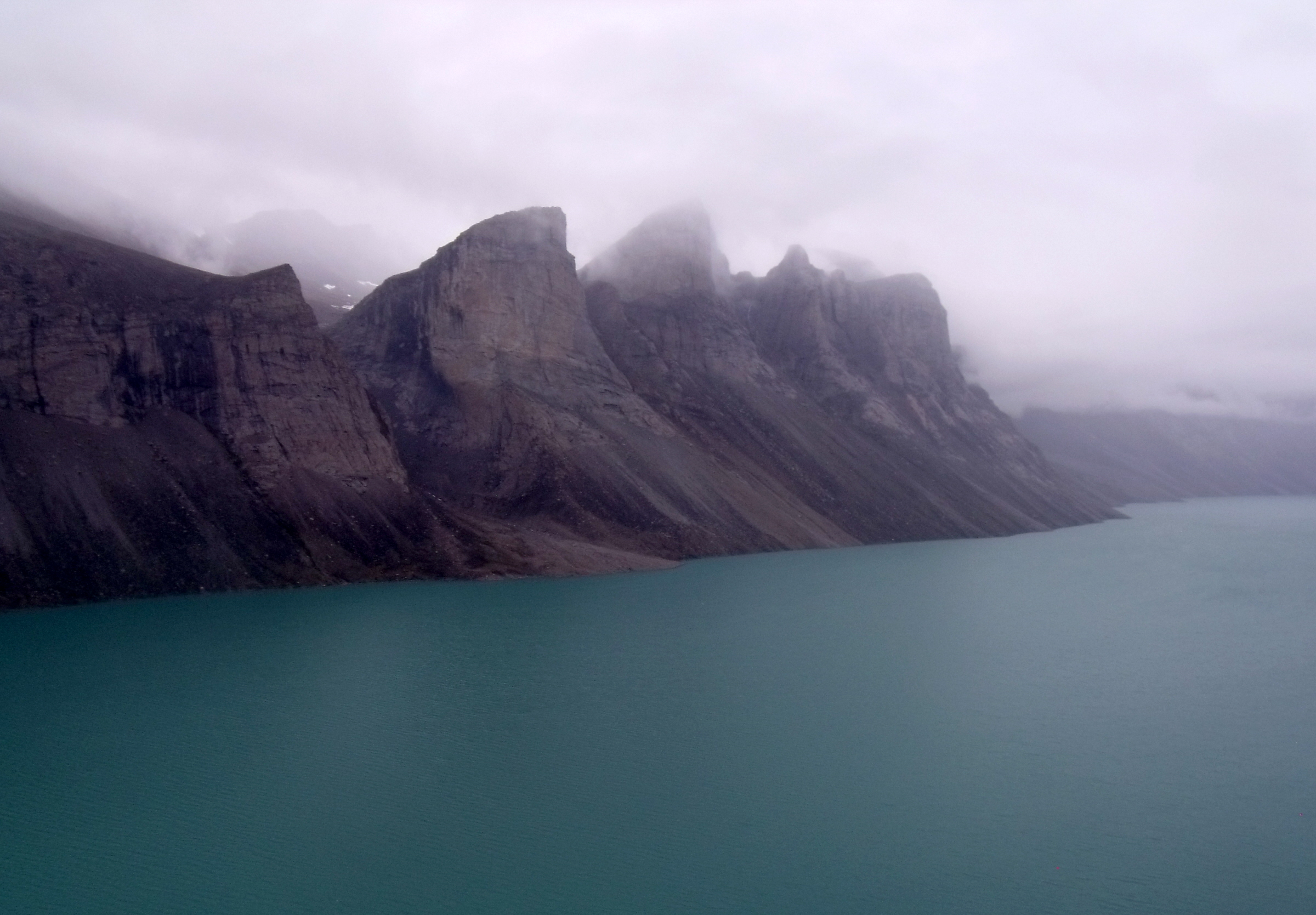 Land-locked freshwater fiord in northern Baffin Island, Nunavut with mile high teeth in the fog. Taken across Ayr Lake from a helicopter returning through the 'back door' to the hamlet of Clyde River. Photo by  Mike Beauregard