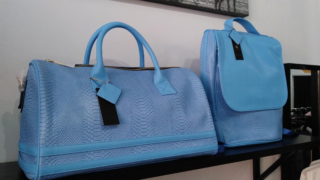 We are 1 of 10 stores nationwide to carry Tote&Carry bags. These are designed by Buffalo born designer, Stitch Dr. (now of Atlanta). These are hand-made of ec0-friendly alligator leather, water-proof, stain & scratch resistant. Sold in-store only. They come in: Sky Blue, Black, Mustard, Orange and Red.  Duffel Bags: $189, Back Pack: $140 (the set together is: $300)