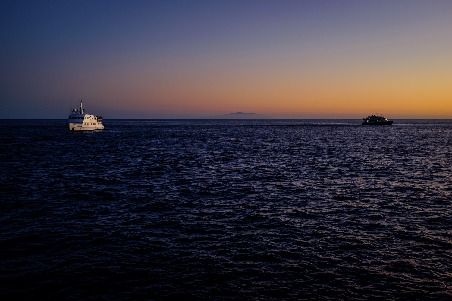 Two live aboard dive boats at sunset...with Socorro Island off in the distance.