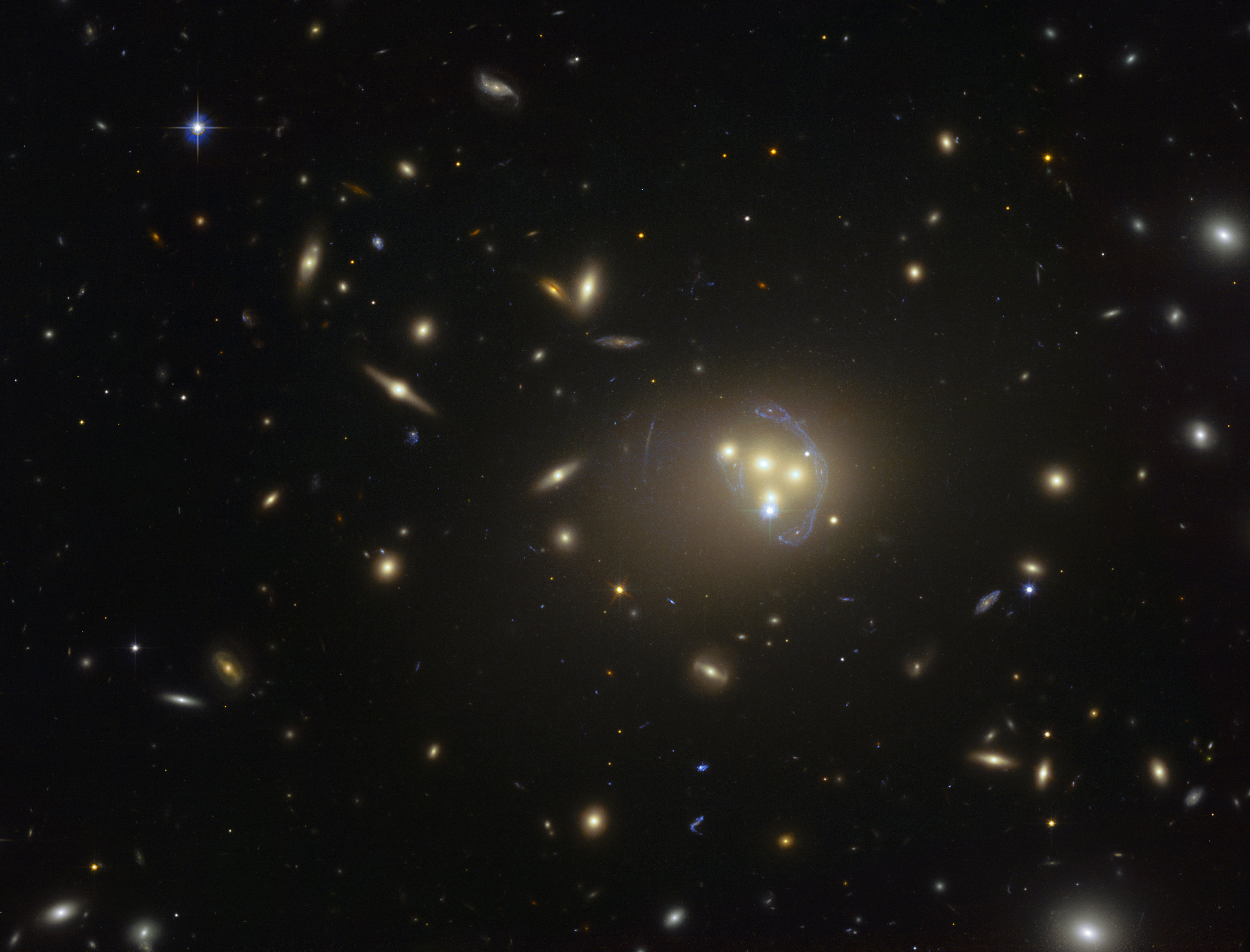 This image from the NASA/ESA Hubble Space Telescope shows the rich galaxy cluster Abell 3827. The strange blue structures surrounding the central galaxies are gravitationally lensed views of a much more distant galaxy behind the cluster. Observations of the central four merging galaxies have provided hints that the dark matter around one of the galaxies is not moving with the galaxy itself, possibly implying dark matter-dark matter interactions of an unknown nature are occuring. Image credit: ESO