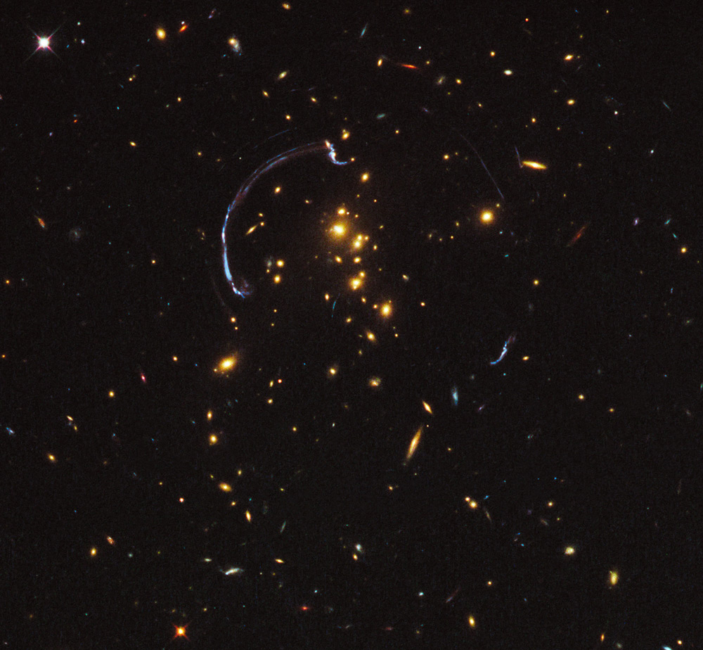 In this image the light from a distant galaxy, nearly 10 billion light-years away, has been warped into a nearly 90-degree arc of light in the galaxy cluster RCS2 032727-132623. The galaxy cluster lies 5 billion light-years away.Image credit: NASA; ESA; J. Rigby (NASA Goddard Space Flight Center); and K. Sharon (Kavli Institute for Cosmological Physics, University of Chicago)