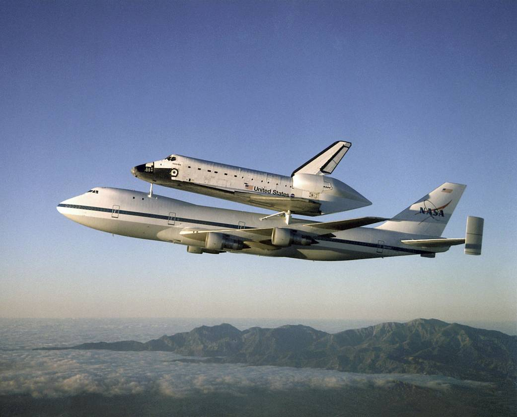 The Space Shuttle orbiter Atlantis, framed by the California mountains, as it rides on the back of one of NASA's Boeing 747 Shuttle Carrier Aircraft (SCA) en route from California to the Kennedy Space Center, Florida. Image credit: NASA