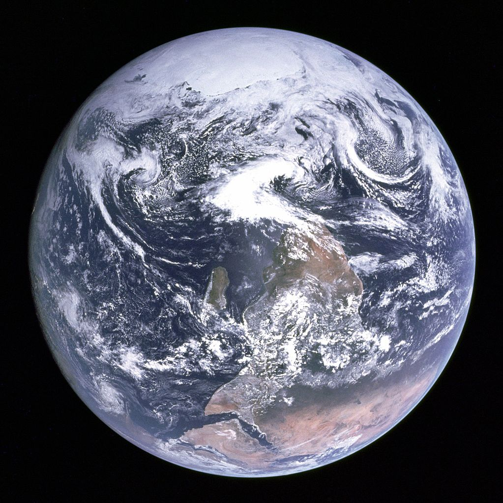 """The Blue Marble"" is a famous photograph of the Earth taken on December 7, 1972, by the crew of the Apollo 17 spacecraft en route to the Moon at a distance of about 29,000 kilometres (18,000 mi). It shows Africa, Antarctica, and the Arabian Peninsula. In this version, it has been flipped upside down, with South at the top of the image. Image credit:  NASA"