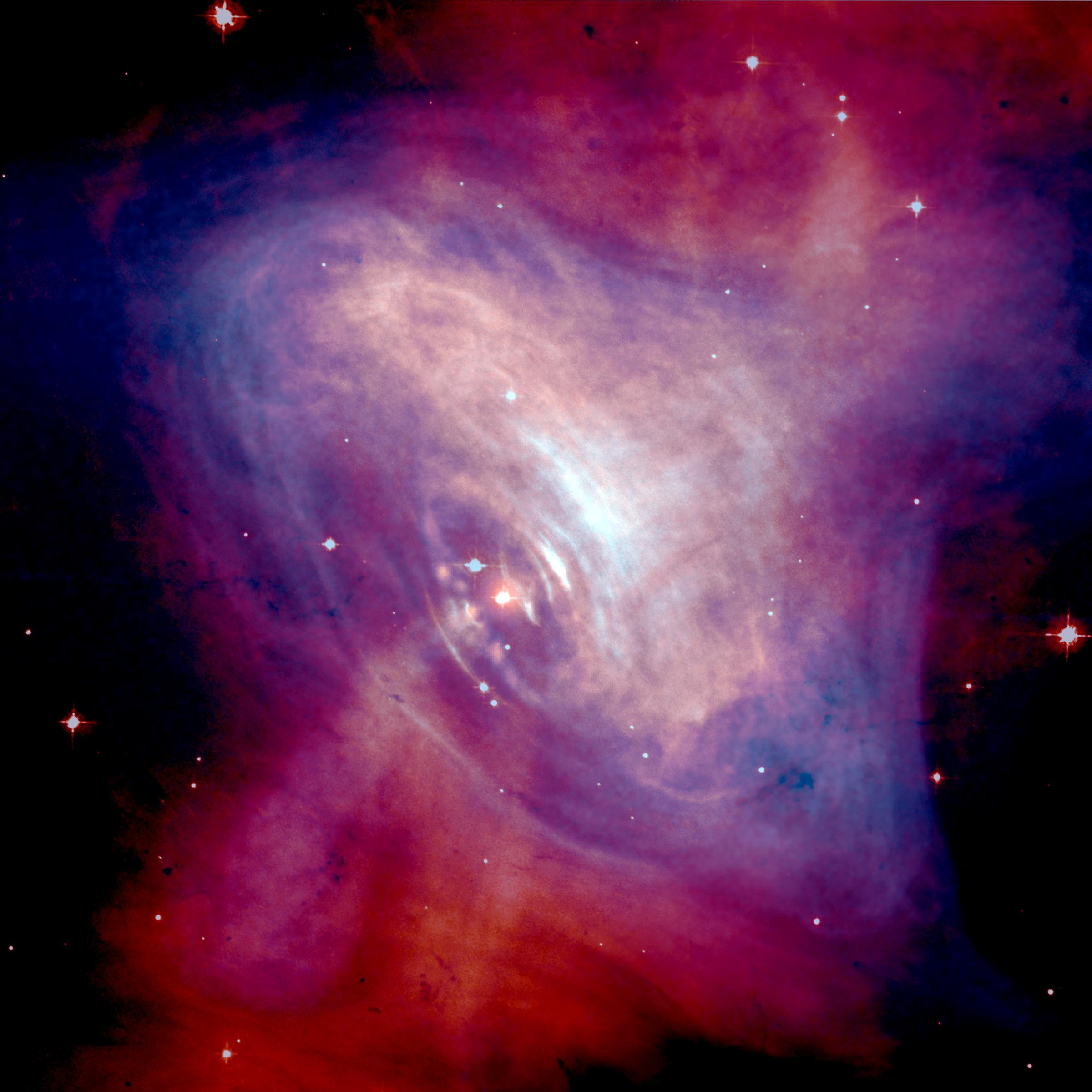 A composite image of the Crab Nebula showing the X-ray (blue), and optical (red) images superimposed. The size of the X-ray image is smaller because the higher energy X-ray emitting electrons radiate away their energy more quickly than the lower energy optically emitting electrons as they move.  Credits for X-ray Image:   NASA  /CXC/ASU/J. Hester et al.; Credits for Optical Image:   NASA  /HST/ASU/J. Hester et al.