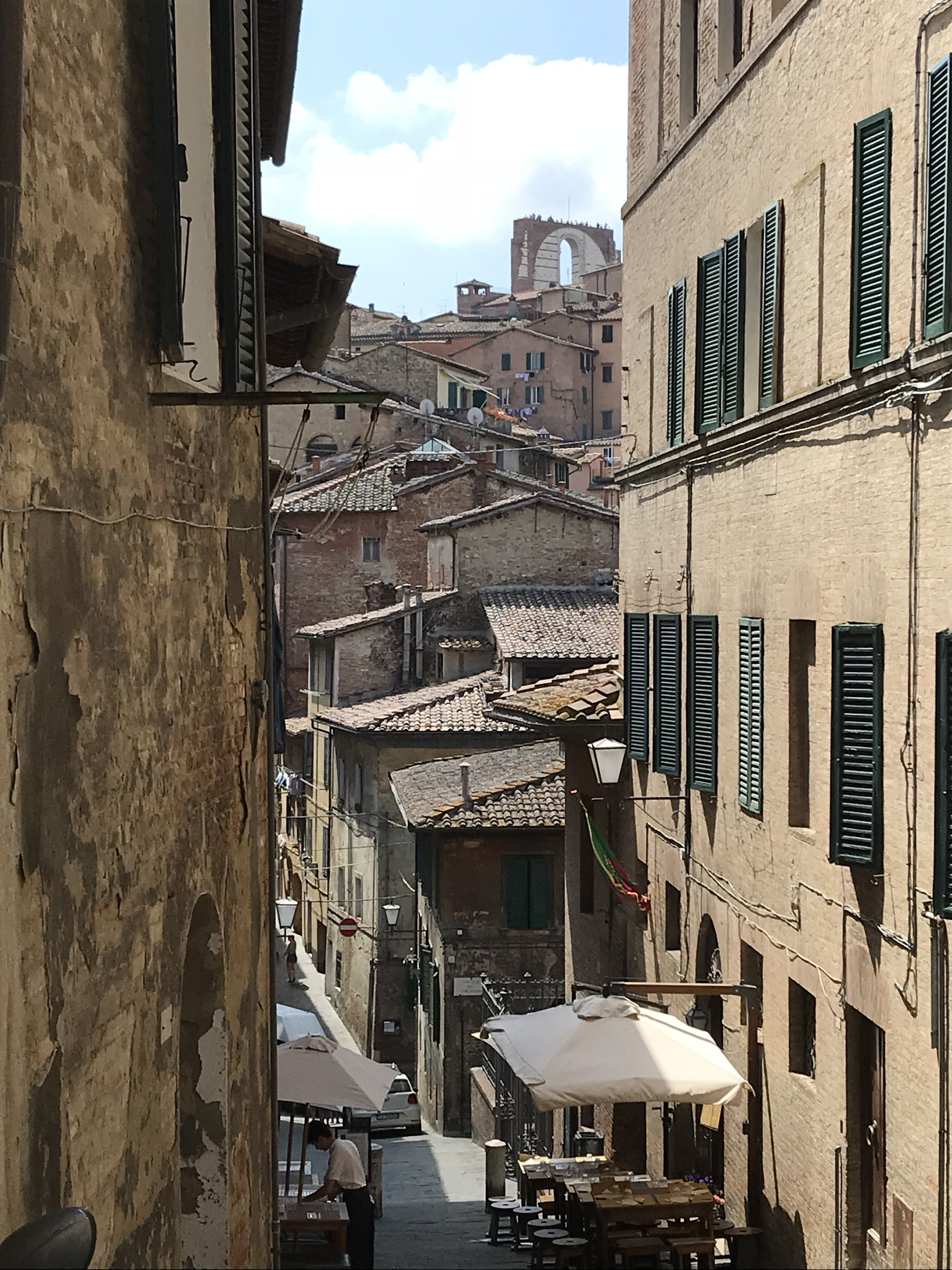 Siena street with outdoor dining and a glimpse of the old city beyond. Photo credit: Mart Martin