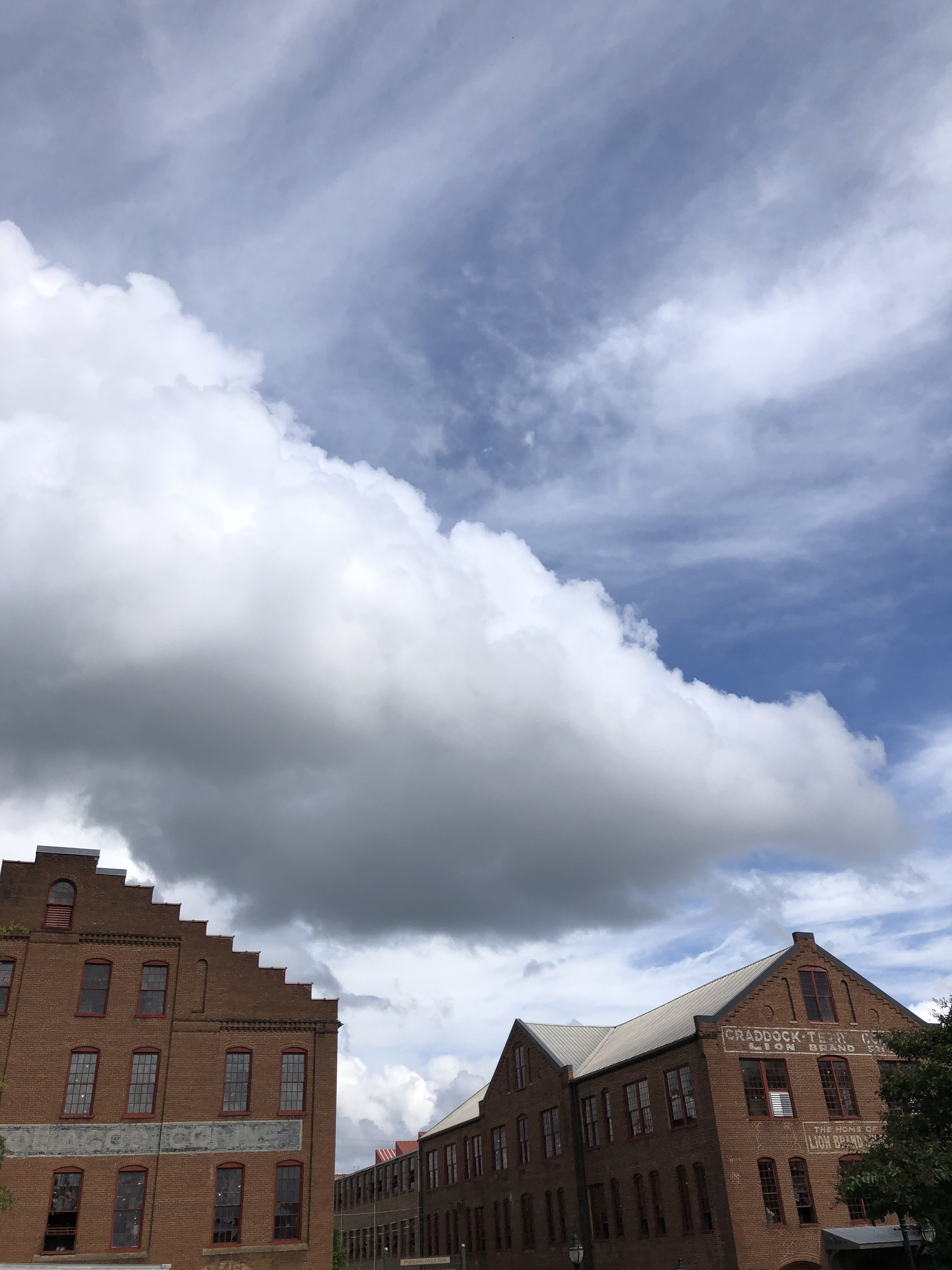 This big cloud looks like it's resting on the rooftops.