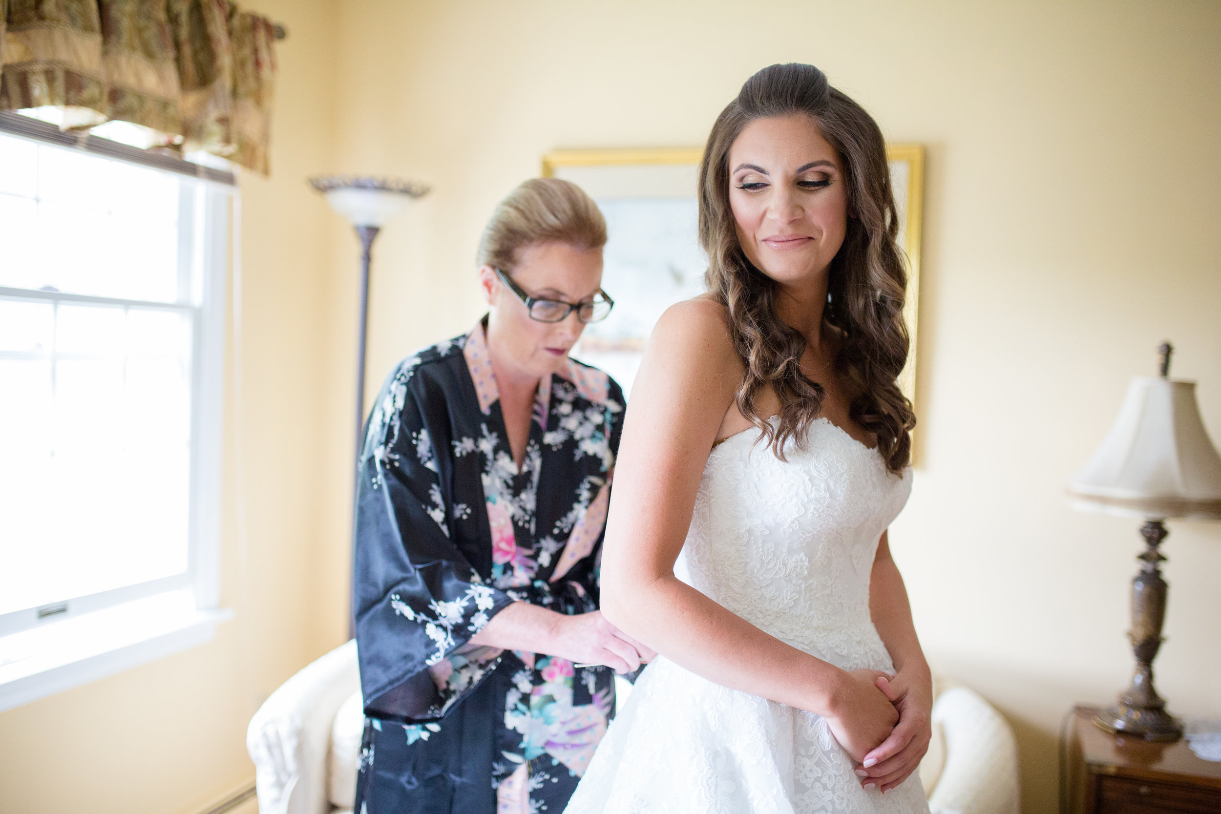 Bride and Mother Getting in Wedding Dress
