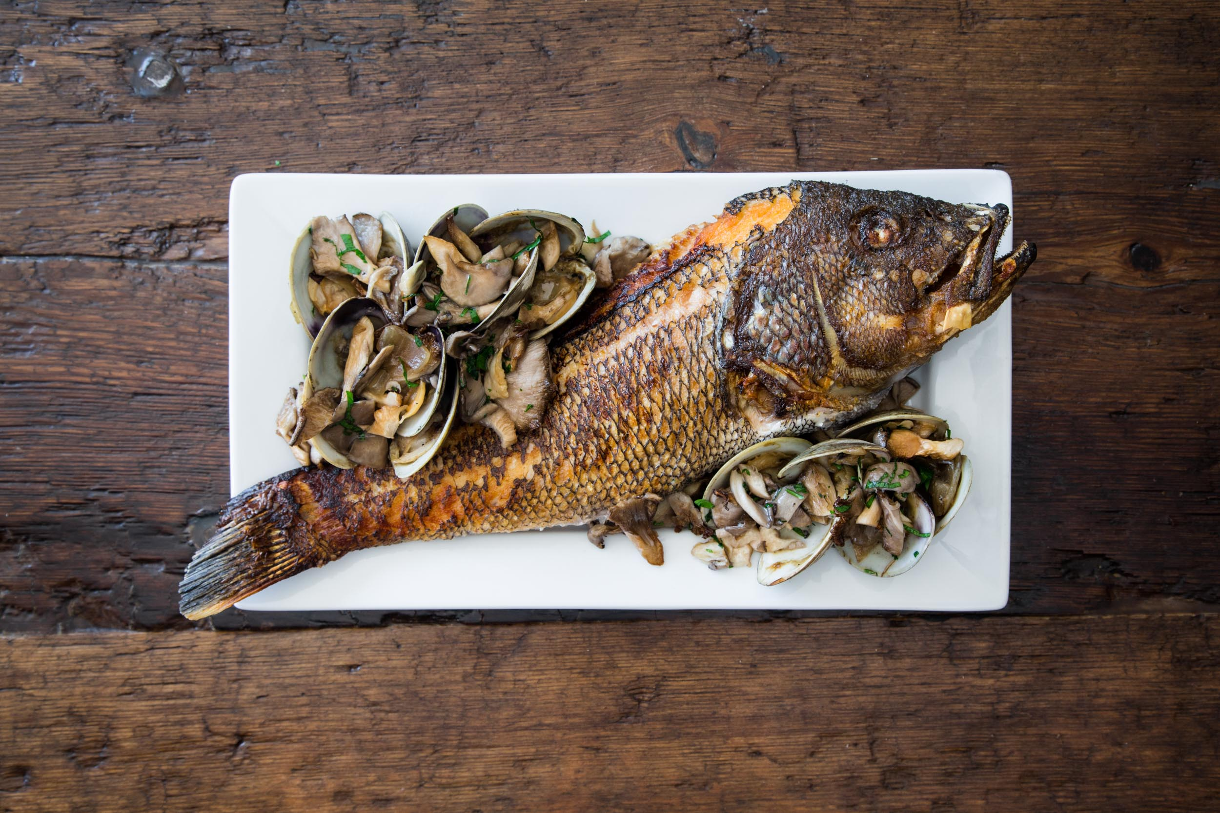 Crispy-Skin Striped Bass topped with a Leek, Wellfleet Clam, Vermouth, and Wild Mushroom Sauce