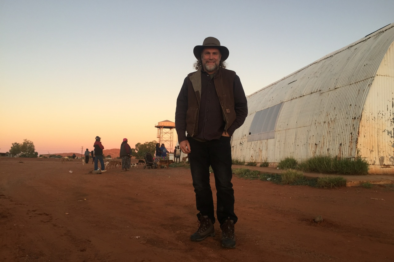 Pictured: Steve standing outside the old hall at Papunya community, Northern Territory. His first concert there was in the winter of 1996.