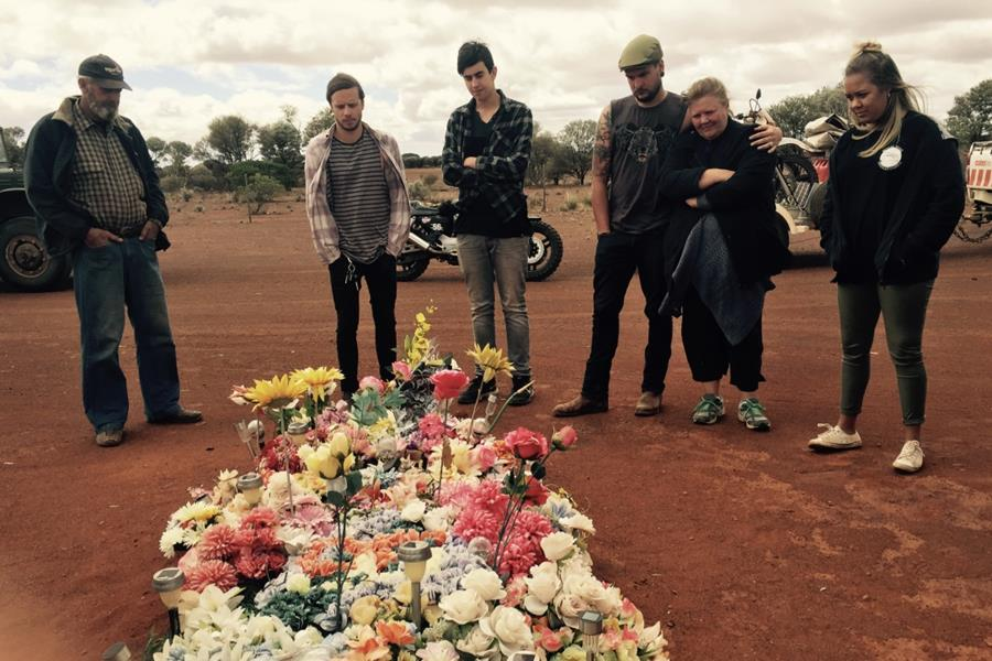 Pictured: Ryan Grace and the team comfort Noleen Mongoo at the gravesite of Ashley Page in Meekathara, WA.