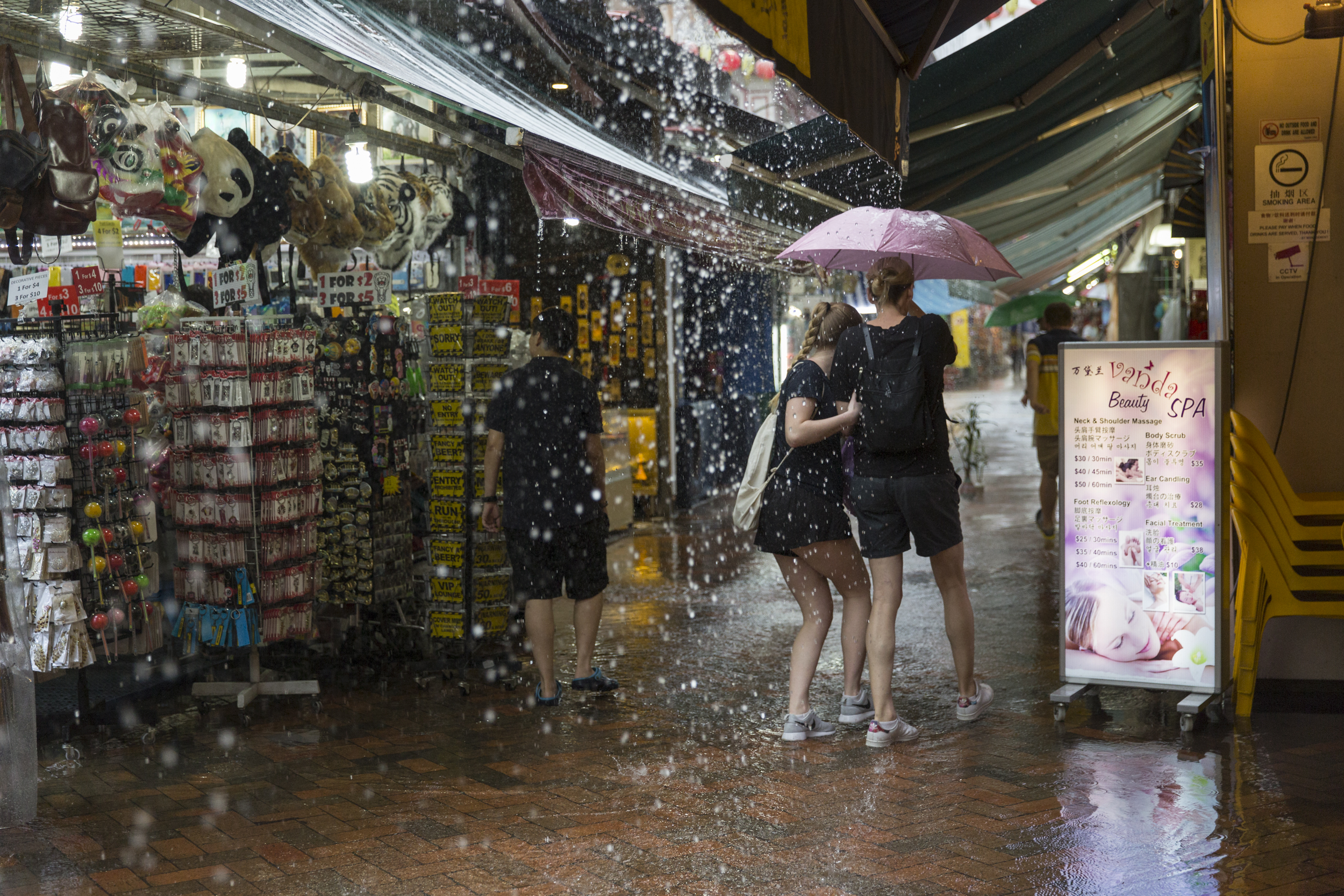 Visitors shield themselves from the sudden downpour in the Chinatown Street Market in Singapore as they try to find more shops under cover on Jan. 2, 2016.The streets quickly flooded forcing vendors to hide their outdoor displays, but many visitors continued shopping despite the rain.