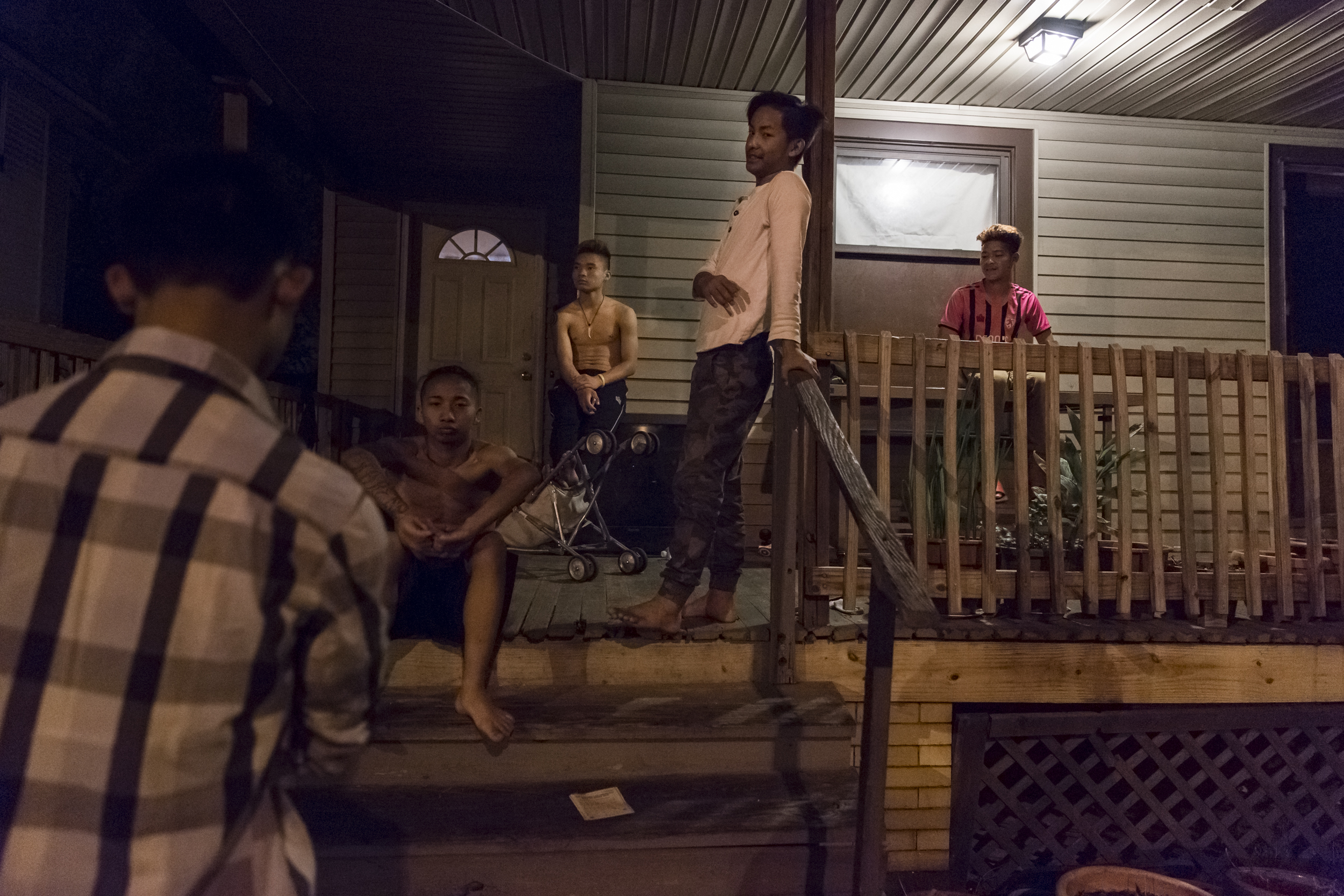 (from left) Ehlerh's Brother The Dah Htoo, Hsar, Joe, Ehlerh, and Hla Ku sit on the porch late at night talking. Although his brother is older, The Dah has strange work hours during the week that make it difficult to make friends, therefore he spends his weekends with Ehlerh and his group of friends. May 9, 2015.